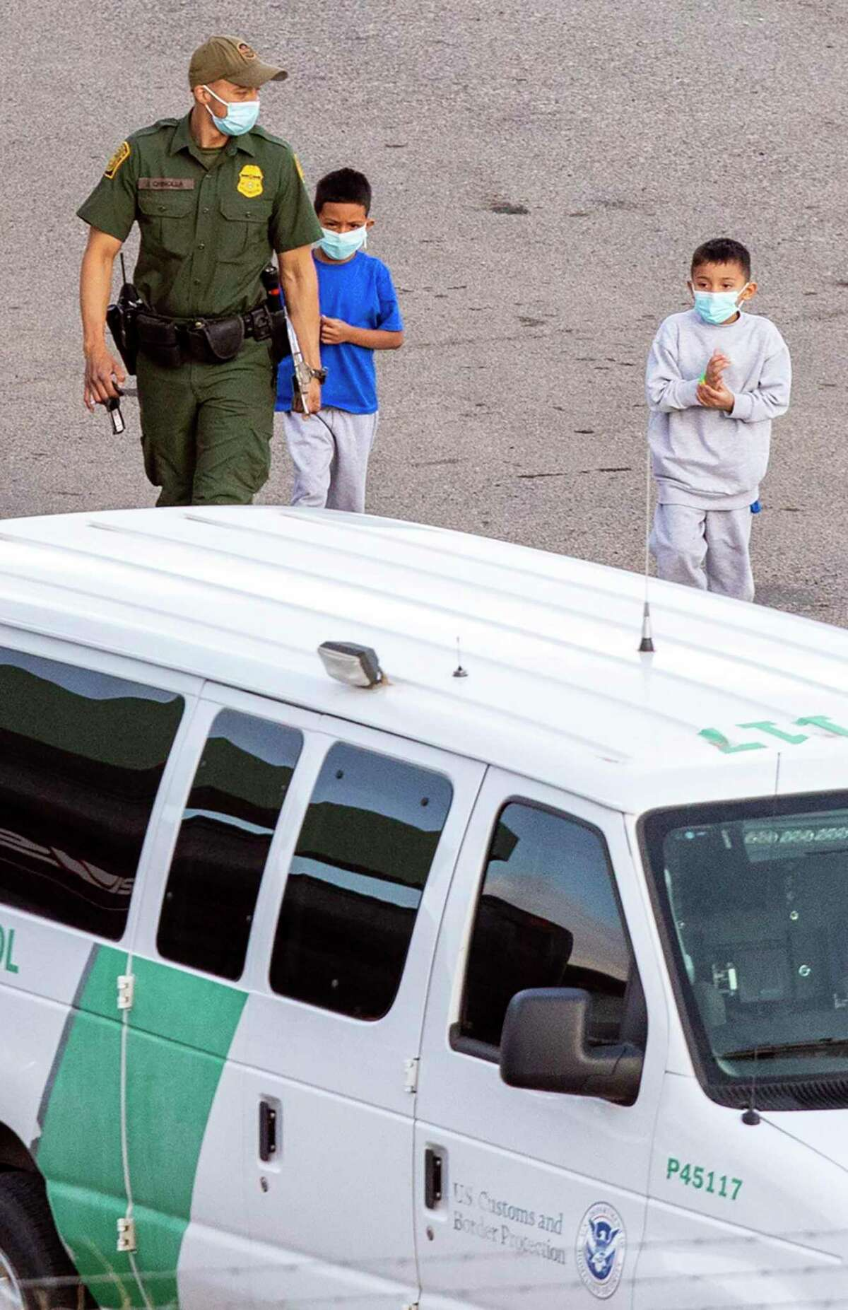 The Customs and Border Patrol processing center in El Paso holds underage and unaccompanied migrant children-male and female,. Two young migrant boys are shown being escorted to a nearby van.