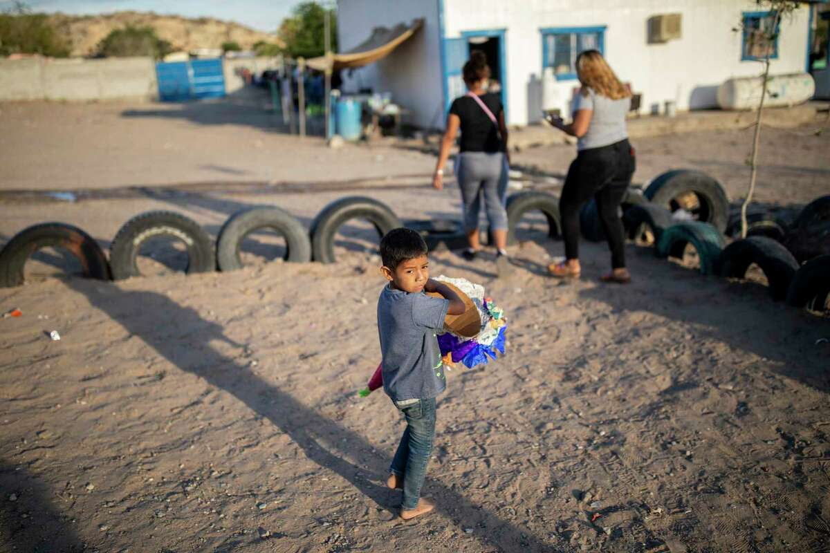 """A young migrant boy wears a piece of a pinata that was used to celebrate the Mexican holiday, """"El Día Del Niño"""", as a toy at a migrant shelter on the outskirts of town, Friday, April 30, 2021, in Juarez."""