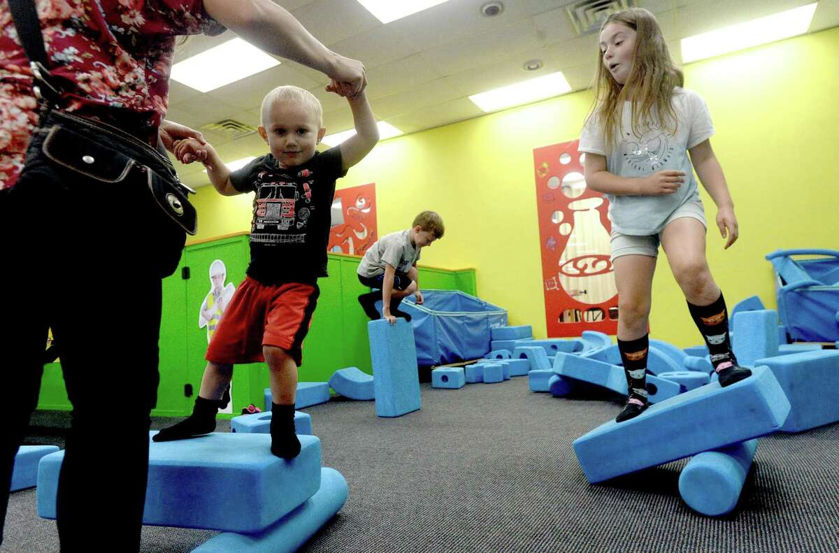 Nikki Caple helps youngest son Otto as he and sister Izzy balance upon the teeter totters they created while playing amid the large foam shapes at the Beaumont Children's Museum Thursday morning. Photo taken Thursday, September 24, 2020 Kim Brent/The Enterprise