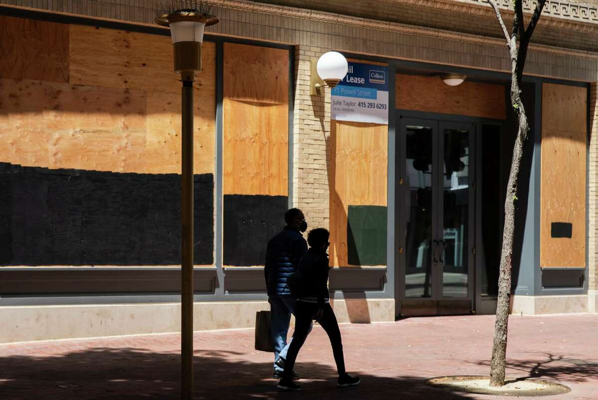 Shoppers walk past a boarded up empty storefront along Powell Street near Union Square in San Francisco. Powell Street, the once-thronged tourist strip, is now defined by empty storefronts post-pandemic.