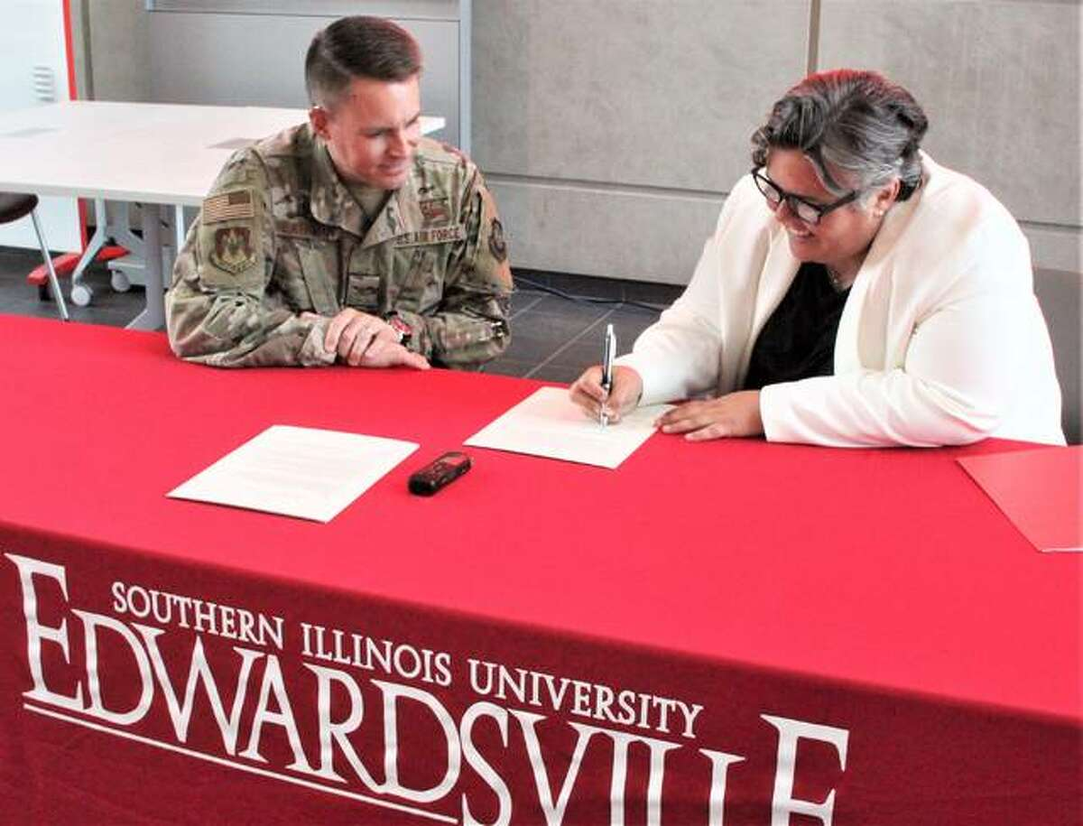 """Col. J. Scot Heathman, commander of the 375th Air Mobility Wing at Scott Air Force Base, in Belleville, watches as Southern Illinois University Edwardsville Provost and Vice Chancellor for Academic Affairs Denise Cobb signs a three-year educational agreement between the university and the unit's """"innovation hub"""" called Elevate. The agreement is designed to allow a formal exchange of expertise and resources between the base and university."""