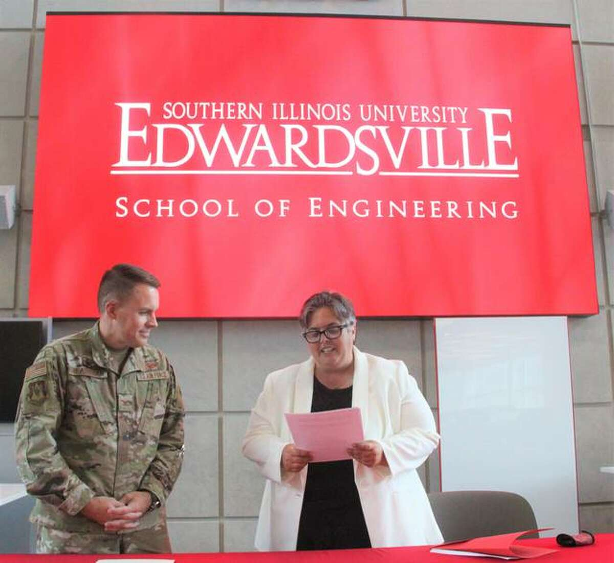 """Col. J. Scot Heathman, commander of the 375th Air Mobility Wing at Scott Air Force Base in Belleville, and .SIUE Provost and Vice Chancellor for Academic Affairs Denise Cobb talk before signing a three-year educational agreement between the university and the unit's """"innovation hub"""" called Elevate."""