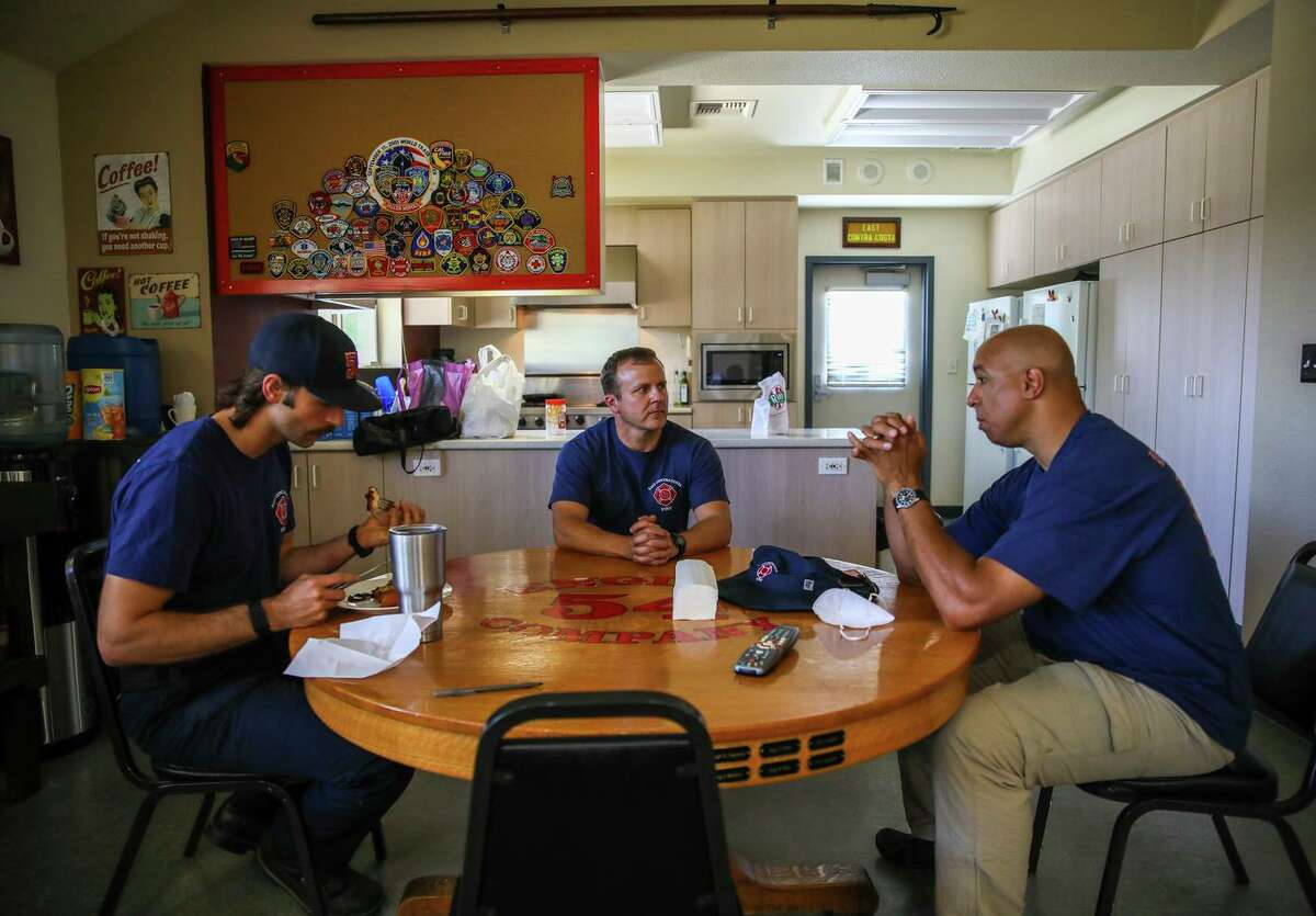 (From left to right) Jared Gavard, 31, of Orangevale, eats a meal as Capt. Robert Ruddick, 44, of Brentwood, and Dr. Malcolm Johnson, 52, of Lafayette, medical director for East Contra Costa Fire, converse at the East Contra Costa Fire Protection District, Station 52, located at 201 John Muir Parkway, on Thursday, June 17, 2021, in Brentwood, Calif. East Contra Costa County only has half the fire infrastructure it needs -- three stations and crews instead of six -- due to decisions made back in the 1970s.
