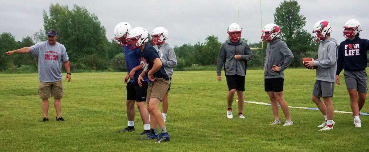 Big Rapids football coach Mike Selzer (left) instructs his players during Thursday night's practice. (Pioneer photo/Joe Judd)