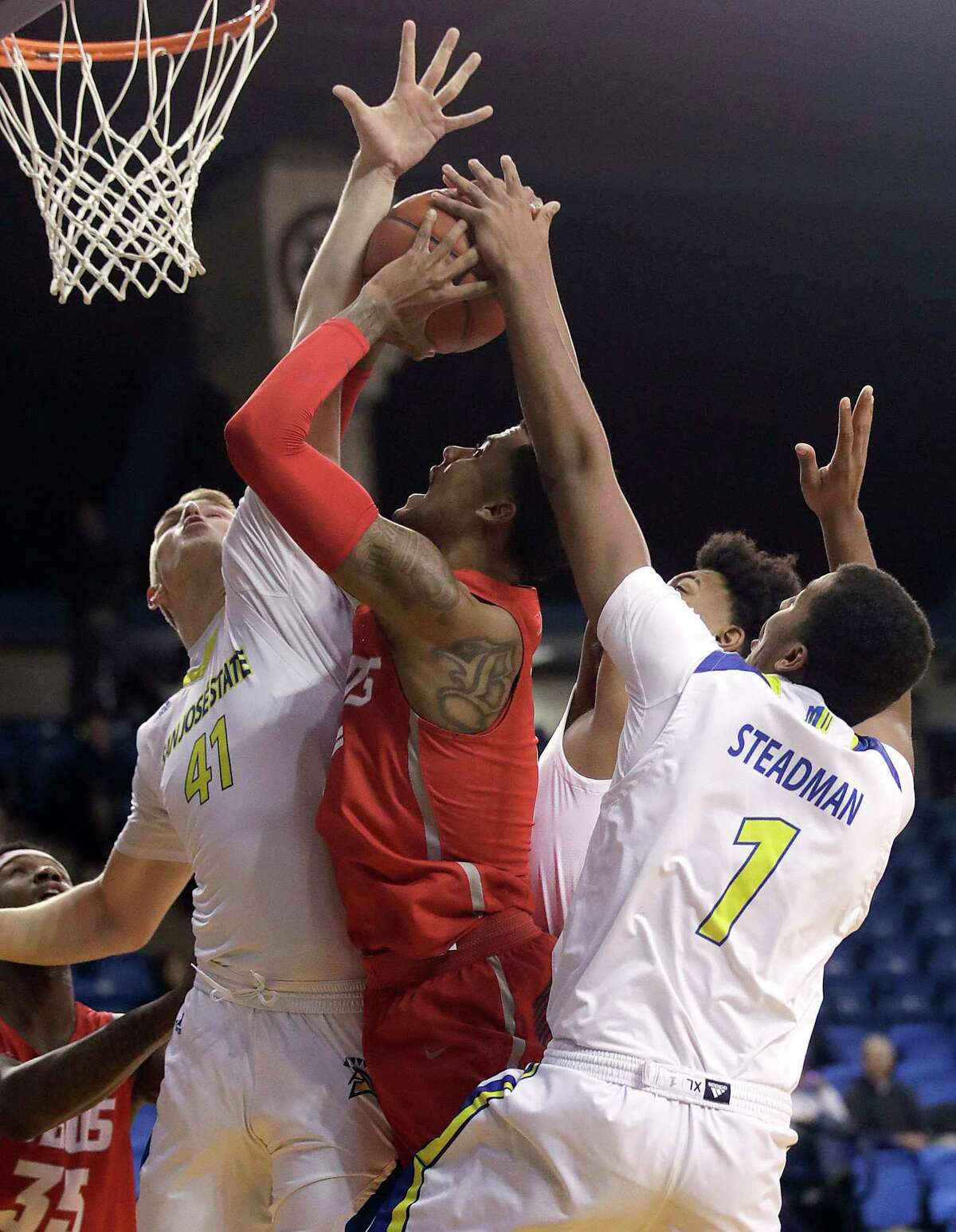 New Mexico forward Vance Jackson, center, shoots between San Jose State center Ashtin Chastain (41) and forward Michael Steadman (1) during a 2019 game.
