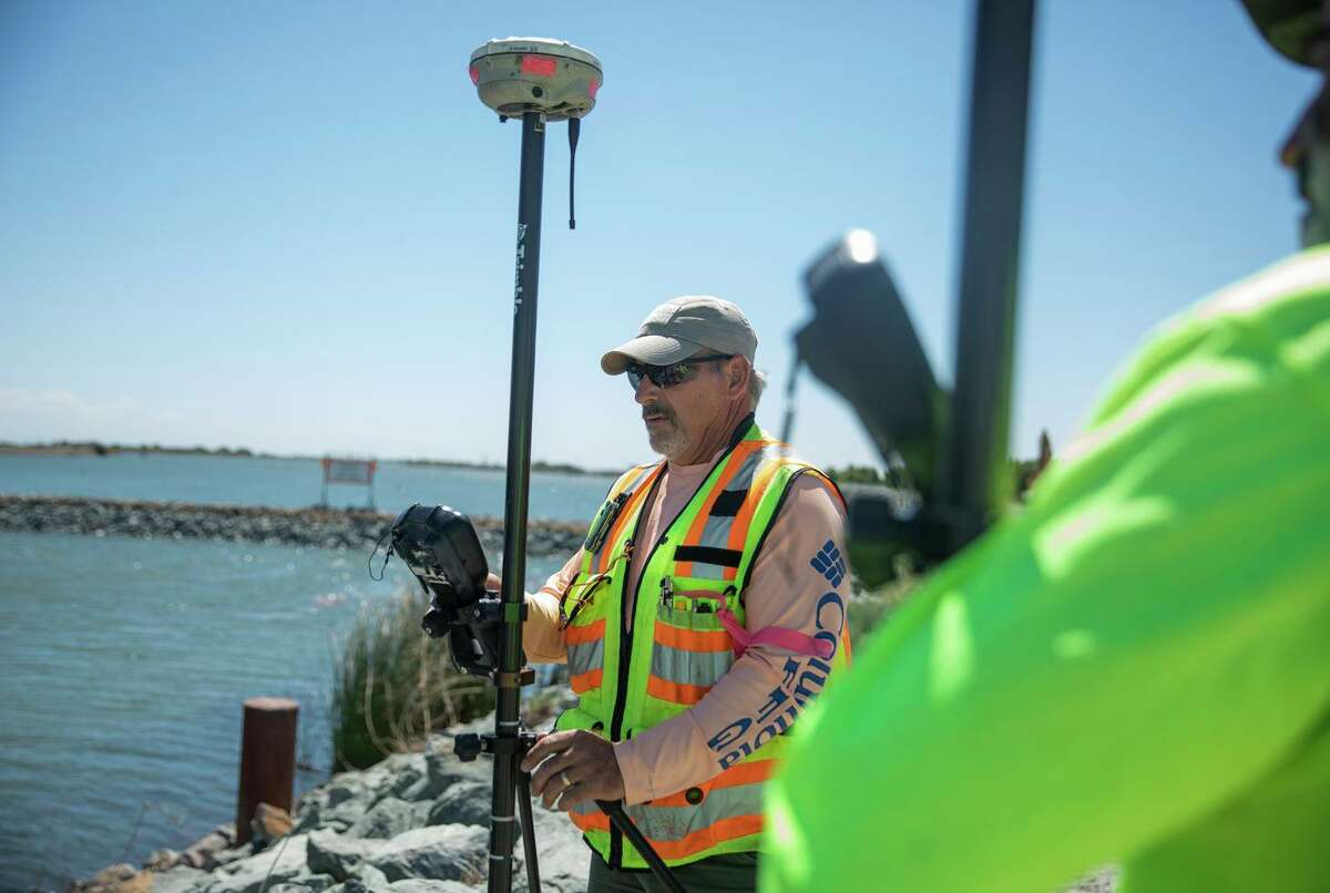 Scott Rebelo, a Department of Water Resources surveyor, takes measurements Thursday of the salinity barrier outside of Oakley.