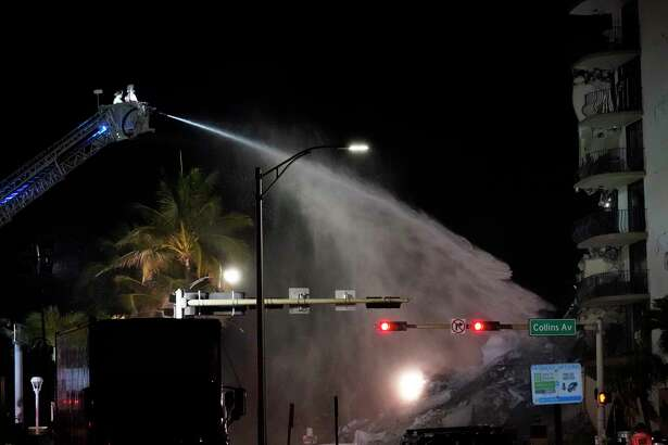 A Miami-Dade Fire Rescue team sprays water onto the rubble as rescue efforts continue where a wing of a 12-story beachfront condo building collapsed, late on Thursday, June 24, 2021, in the Surfside area of Miami.