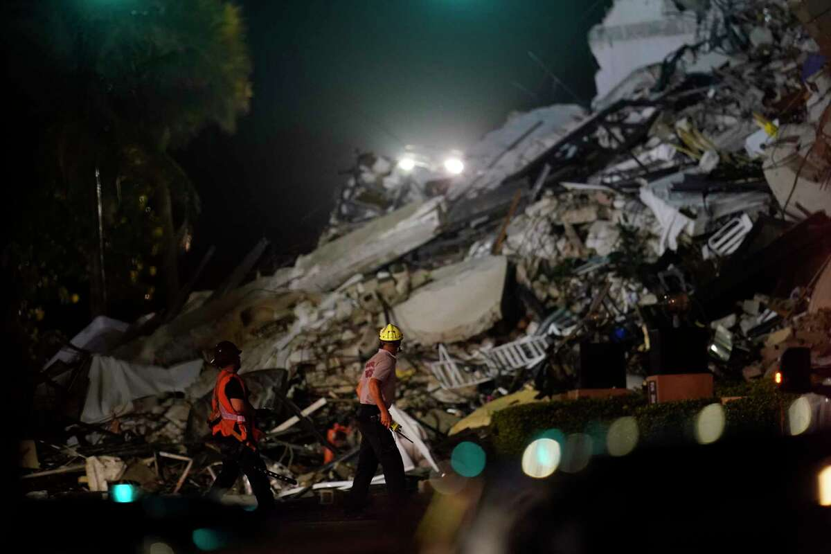 Rescue workers walk beside the rubble as rescue efforts continue where a wing of a 12-story beachfront condo building collapsed, Thursday, June 24, 2021, in the Surfside area of Miami.