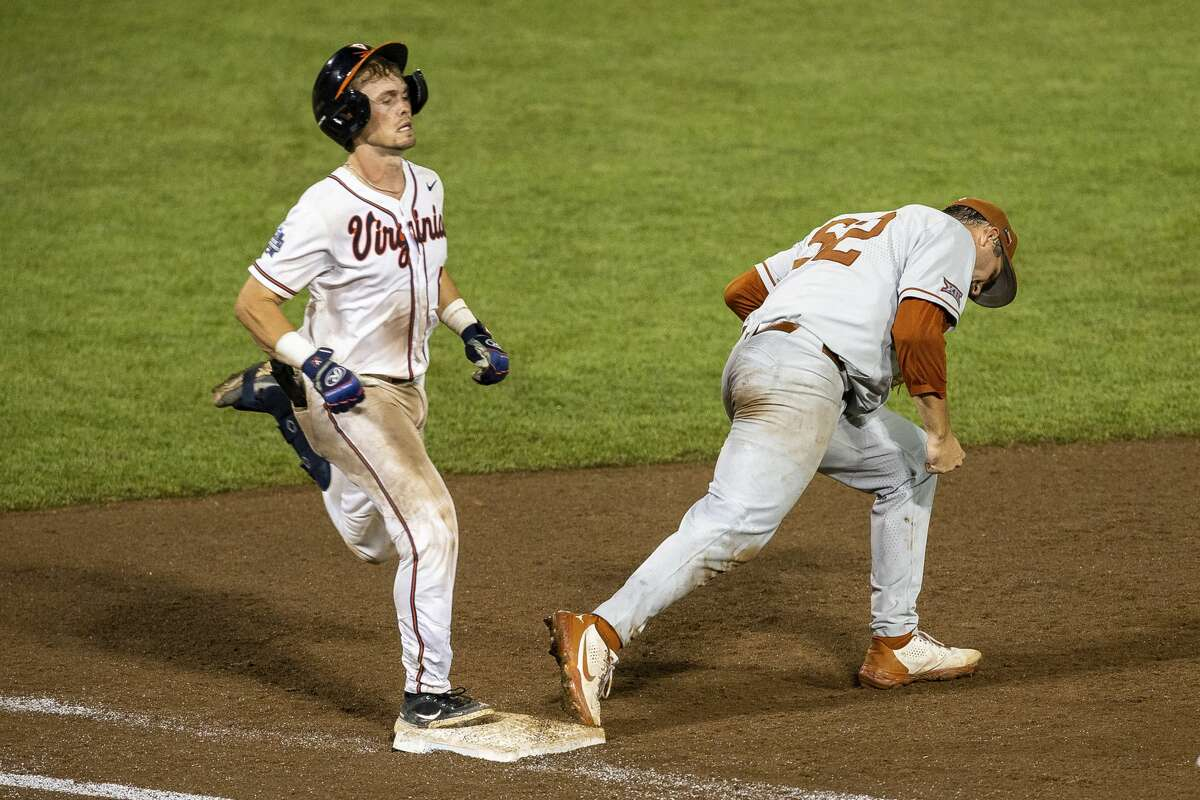 Texas' Zach Zubia (52) forces out Virginia's Logan Michaels (12) for the last out in the ninth inning during a baseball game in the College World Series Thursday, June 24, 2021, at TD Ameritrade Park in Omaha, Neb. (AP Photo/John Peterson)