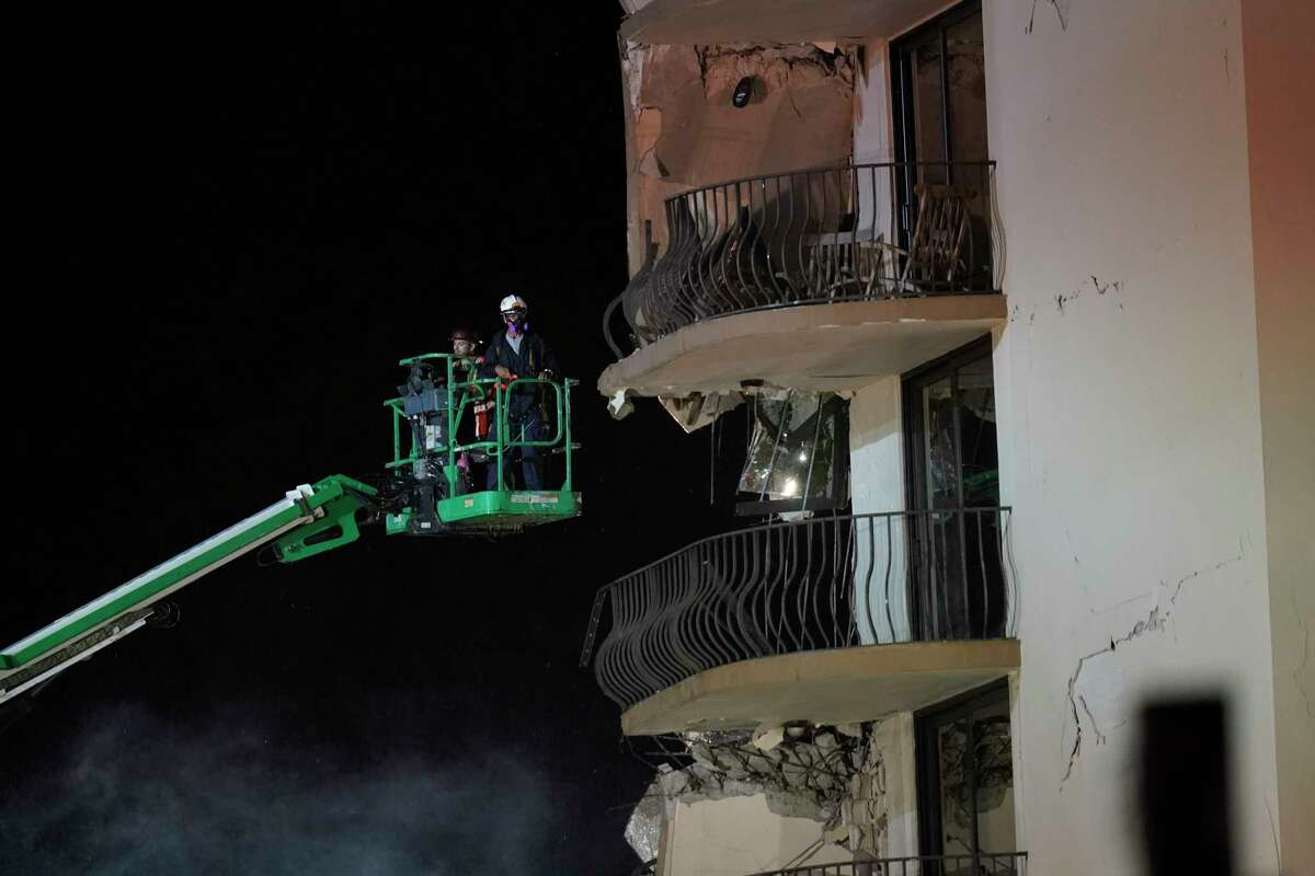 Workers use a lift to investigate balconies in the still-standing portion of the building, as rescue efforts continue where a wing of a 12-story beachfront condo building collapsed, late on Thursday, June 24, 2021, in the Surfside area of Miami.