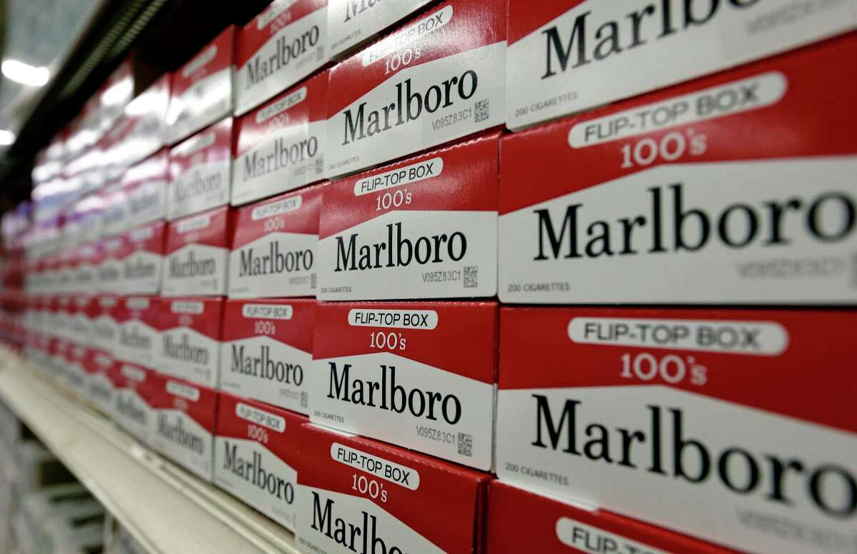 This June 14, 2018 file photo shows cartons of Marlboro cigarettes on the shelves at JR outlet in Burlington, N.C. Philip Morris International, which sells Marlboro cigarettes outside the U.S., has announced that it plans to relocate its headquarters from New York City to Connecticut.