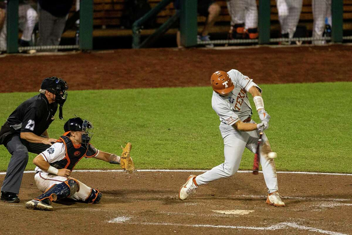 Texas' Ivan Melendez (17) singled up the middle to bring in a run by Mike Antico (5) in the eighth against Virginia during a baseball game in the College World Series Thursday, June 24, 2021, at TD Ameritrade Park in Omaha, Neb. (AP Photo/John Peterson)