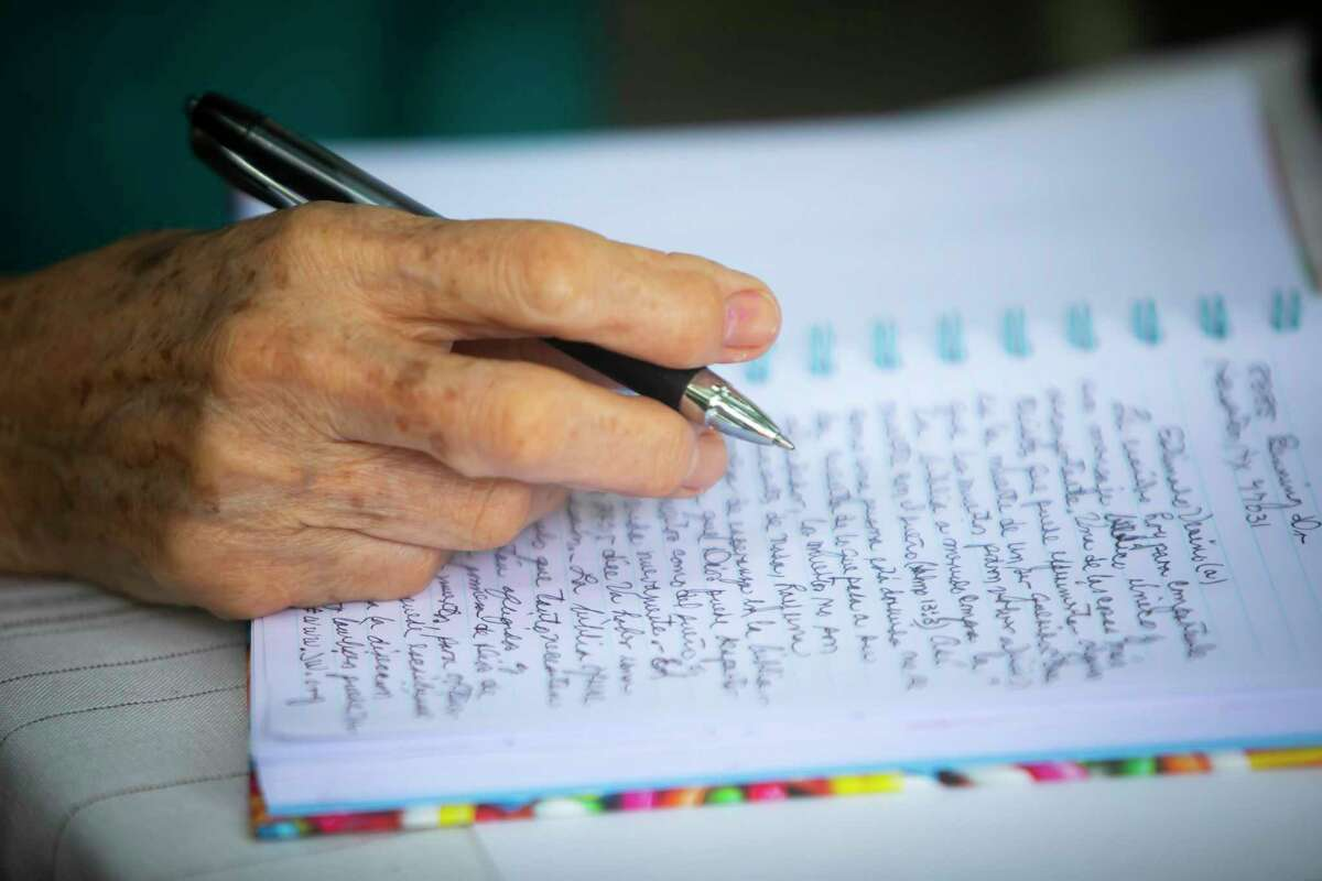 Raquel Sanchez writes a letter to a prisoner as a part of a prison ministry outside her home on Monday, June 7, 2021. The Sanchezes, who are Jehovah's Witnesses, switched from meeting prisoners in-person to letter-writing during the pandemic.