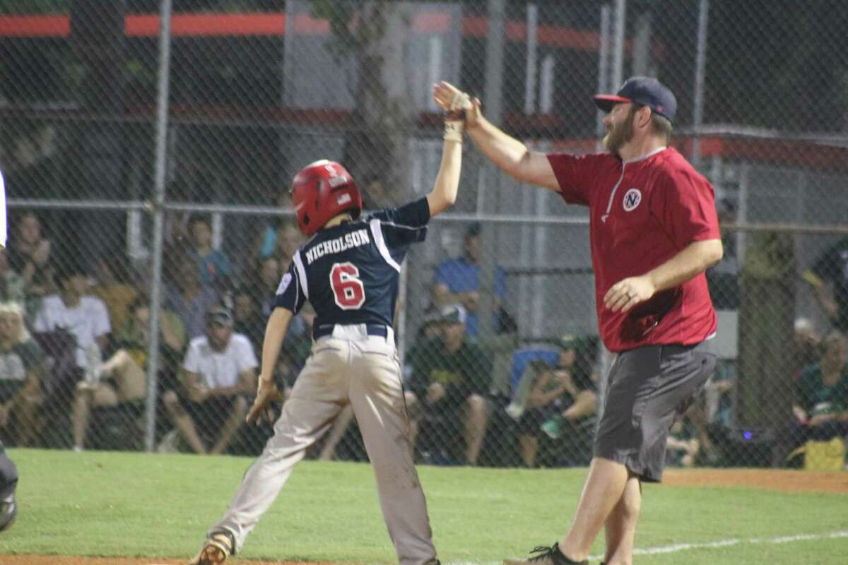 NASA Area Little League 11s manager Mike Howard joyously welcomes Ryan Nicholson to third base after the youngster belted a two-RBI triple during a five-run fourth inning Thursday night.