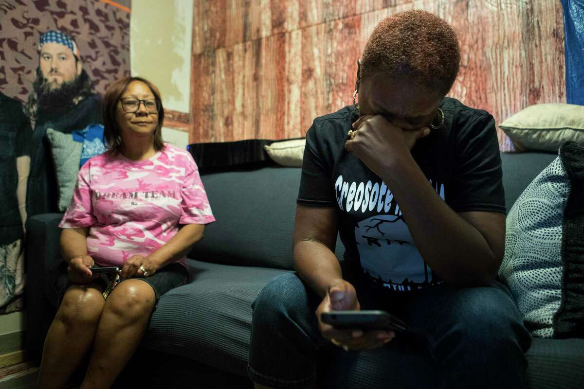 Sandra Edwards, right, reacts as she looks at a photo on her phone of a friend, who is hospitalized with cancer, as she sits with Dianna Cormier-Jackson in Edwards' 5th Ward home Wednesday, June 23, 2021 in Houston. Edwards' home sits in the middle of a cancer cluster near a rail yard that creosote contamination is blamed for several cancer related deaths.