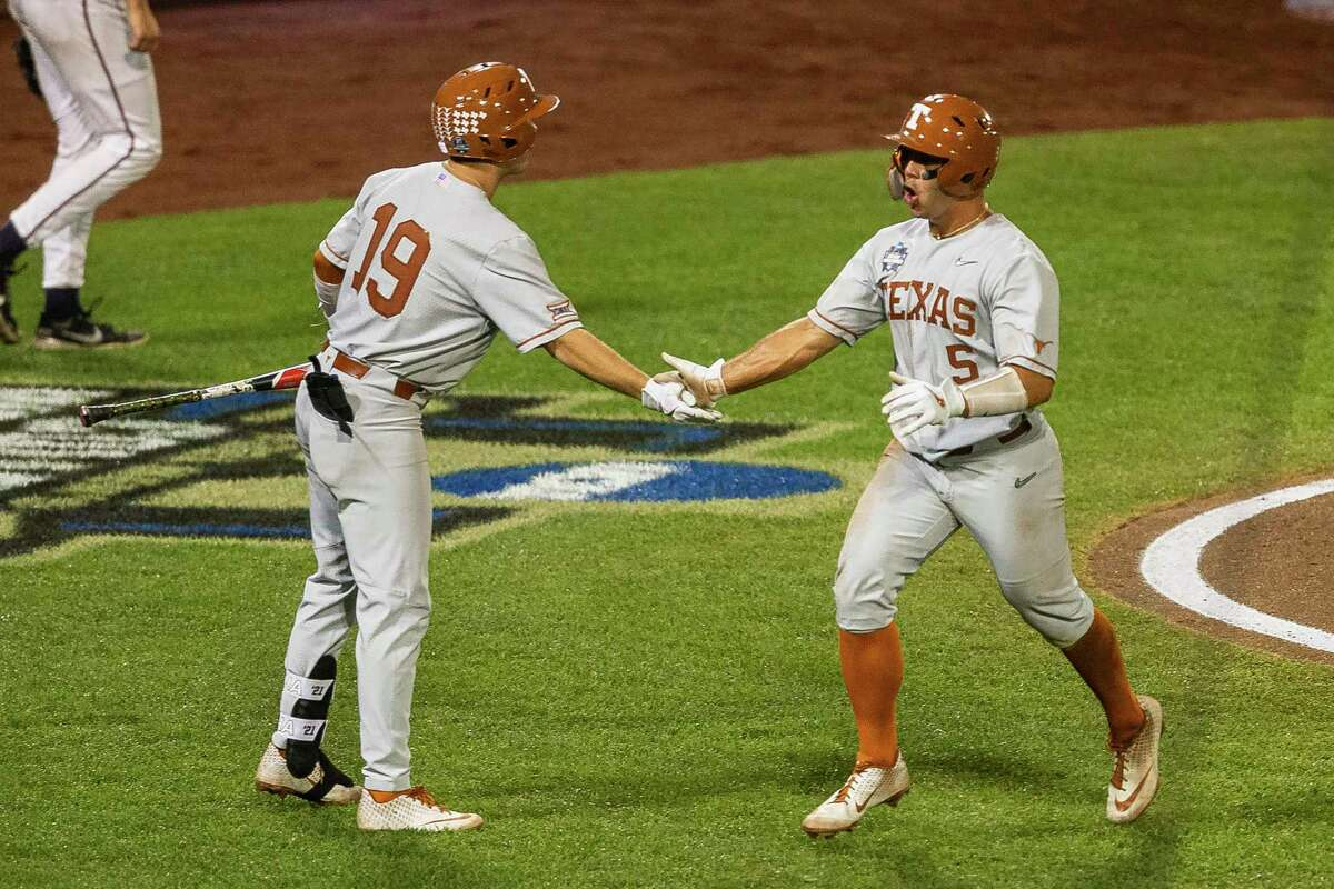Texas' Mike Antico (5) gets five from Mitchell Daly (19) celebrating his run against Virginia in the eighth during a baseball game in the College World Series Thursday, June 24, 2021, at TD Ameritrade Park in Omaha, Neb. (AP Photo/John Peterson)
