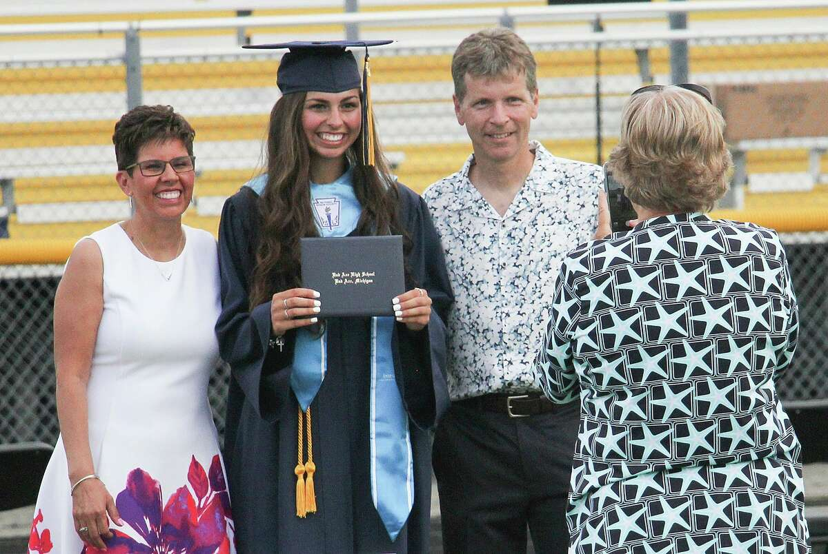 Mark Prescott, Bad Axe High School girls tennis coach, poses for a photo with his wife, Maria, and daughter, Jelena, following Bad Axe High School's 2020 commencement ceremony. Mark Prescott, Bad Axe High School girls tennis coach, died Wednesday in a cycling accident west of Bad Axe. (Tribune File Photo)