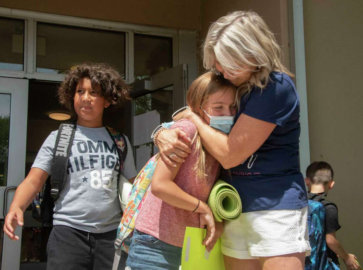 Retiring teacher Lisa Ethier hugs her student Isla Tebordo, 8, after Ethier was surprised on her last day with a bagpipe parade with friends, family and students at Abram Lansing Elementary School on Friday, June 25, 2021 in Cohoes, N.Y. Lisa's husband Gary Ethier organized the event. (Lori Van Buren/Times Union)