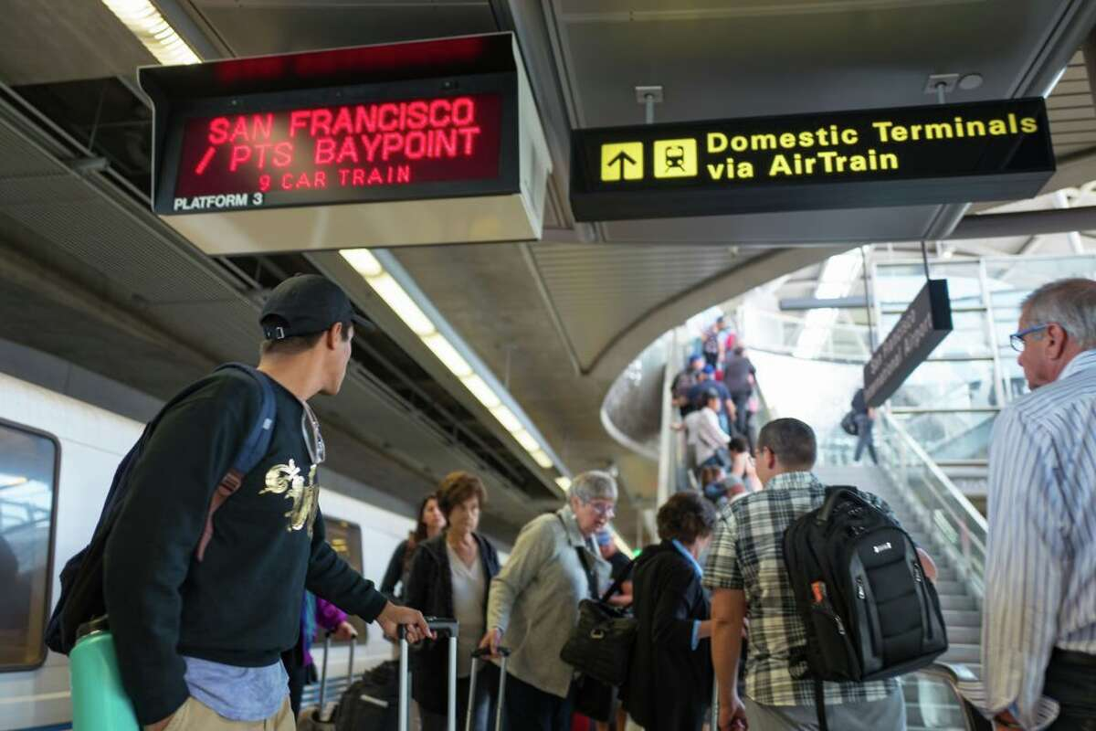A large crowd of passengers exits a BART train at San Francisco International Airport and takes an escalator towards the airport terminal on Sept. 13, 2017.