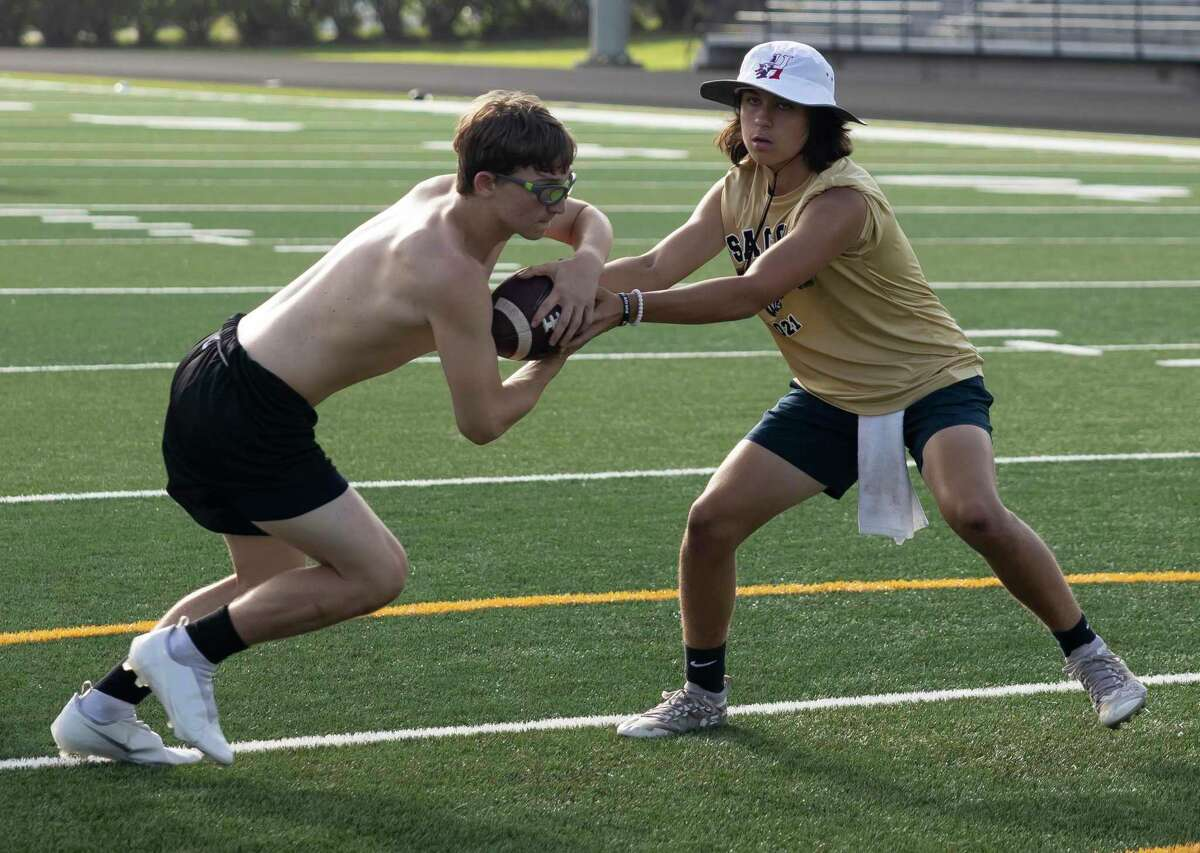 Sam Buzbee, right, practices handoffs with teammate Dylan Bullock during Strength and Conditioning camp at Buddy Moorhead Stadium, Thursday, June 24, 2021, in Conroe. Last summer, these camps were one of the first things to return, though deeply impacted by the COVID-19 pandemic.