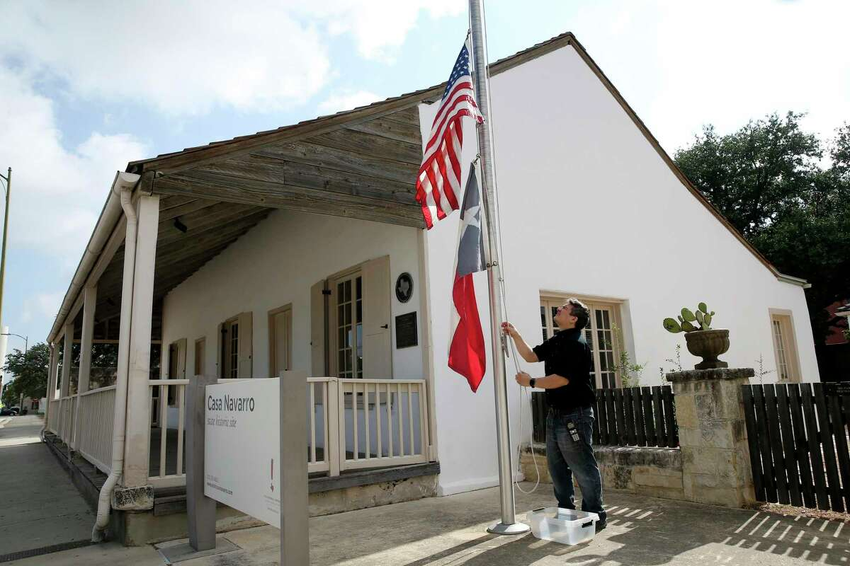 Lester Velazquez, 34, raises the U.S. and Texas flags Casa Navarro Historic Site as it reopens, Friday, June 25, 2021. The site closed in August 2020 due to the demolition of the Central Texas Detention Facility next door. The half-acre site has a cluster of historic structures where Jose Antonio Navarro, one of two Tejanos who signed the Texas Declaration of Independence, lived and operated a store in the 1800s. Valazquez is a customer service representative at the site.
