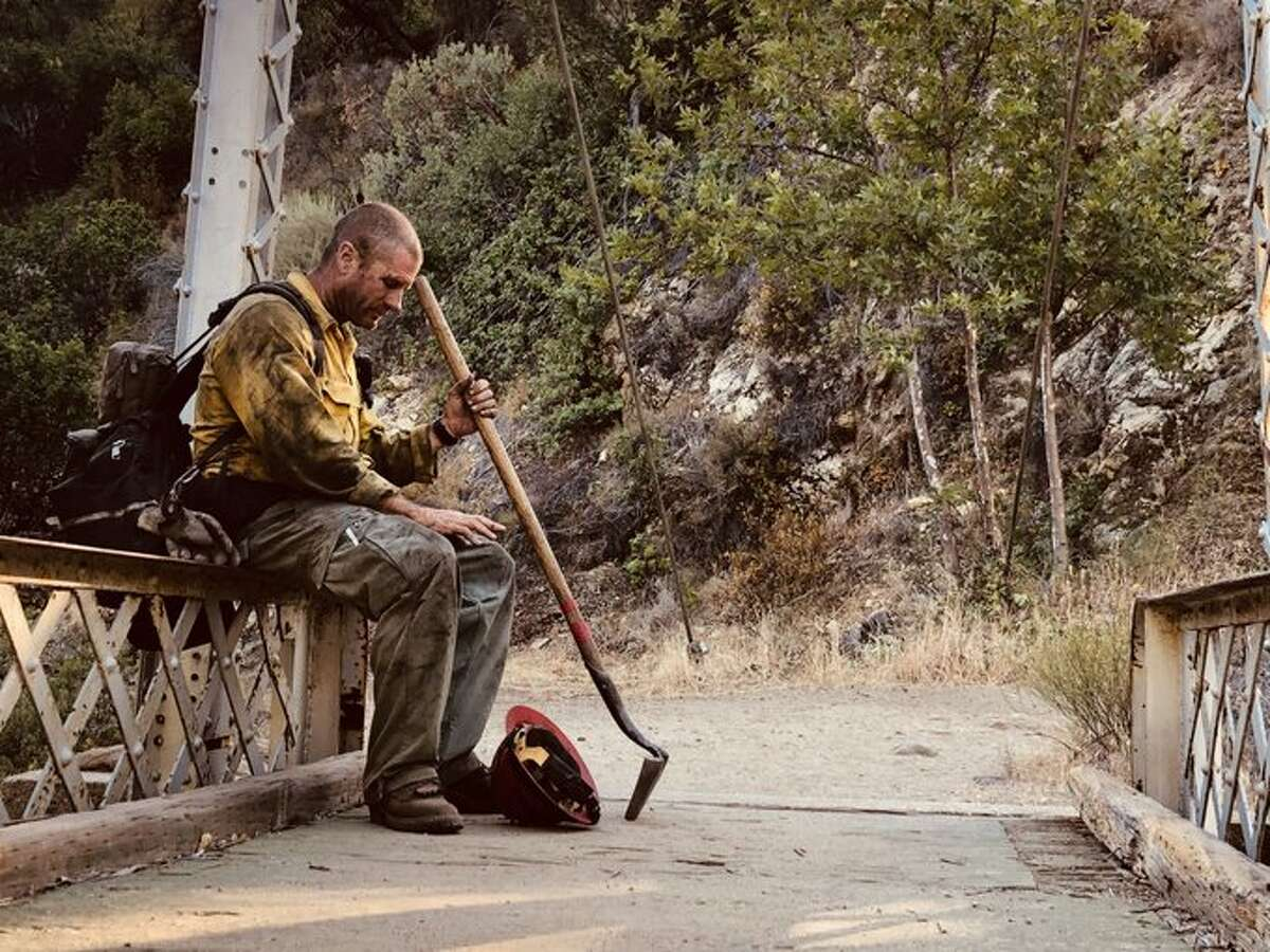 Justin Grunewald, a U.S. Forest Service Hotshot captain of Mill Creek's Crew 4, pauses for a moment after more than a week of battling flames in the Willow Fire near Big Sur, June 2021.
