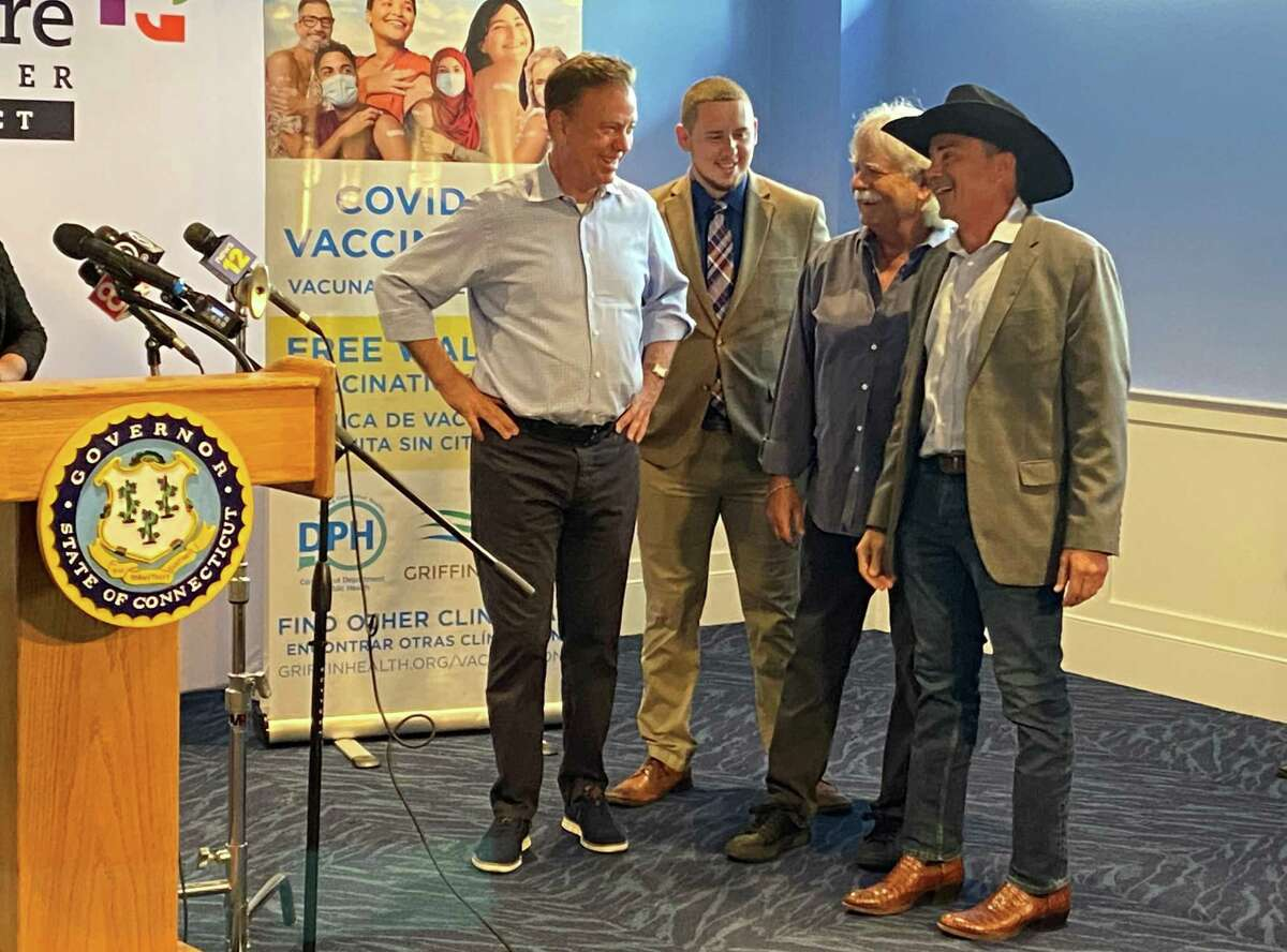 Gov. Ned Lamont chats with State Rep. Antonio Felipe, D-130, concert promoter Jim Koplik and Bridgeport Mayor Joseph Ganim during Friday's announcement of the state's Rock the Shot vaccination incentive program.