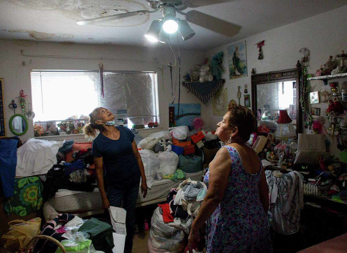 Corrina Jimenez, left, looks up at the rotten ceiling found in a room inside the apartment of Blanca Lydia Martinez, right, at Victoria Manor Apartments on Friday, June 18, 2021, in Houston. Several COVID-19 relief measures are set to end soon, including an eviction moratorium and unemployment benefits.