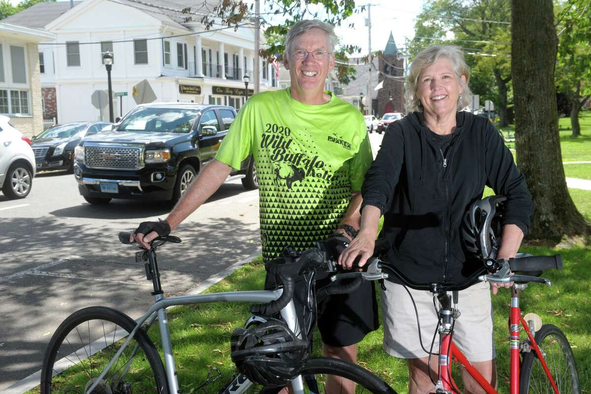 Steve and Patricia Hauser pose with their bicycles on the Milford Green, in Milford, Conn. June 23, 2021. The Hausers are part of a group of bicycle enthusiasts advocating for safe bicycle lanes around the city.