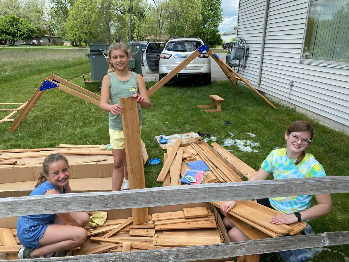 Lulu Church, Hailey Swingle and Sara Church organize pieces of the new playset at Midland Eagles Aerie 2110 in May.