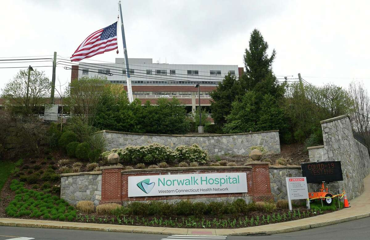J&K Tree Service sets up a crane to display a large American Flag and a thank you note for Norwalk Hospital staff Wednesday, April 8, 2020, in Norwalk, Conn.