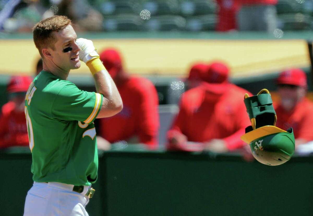 Mark Canha (20) tosses his helmet and guard in frustration after striking out looking to end the fourth inning as the Oakland Athletics played the Los Angeles Angels at the Coliseum in Oakland, Calif., on Sunday, May 30, 2021.