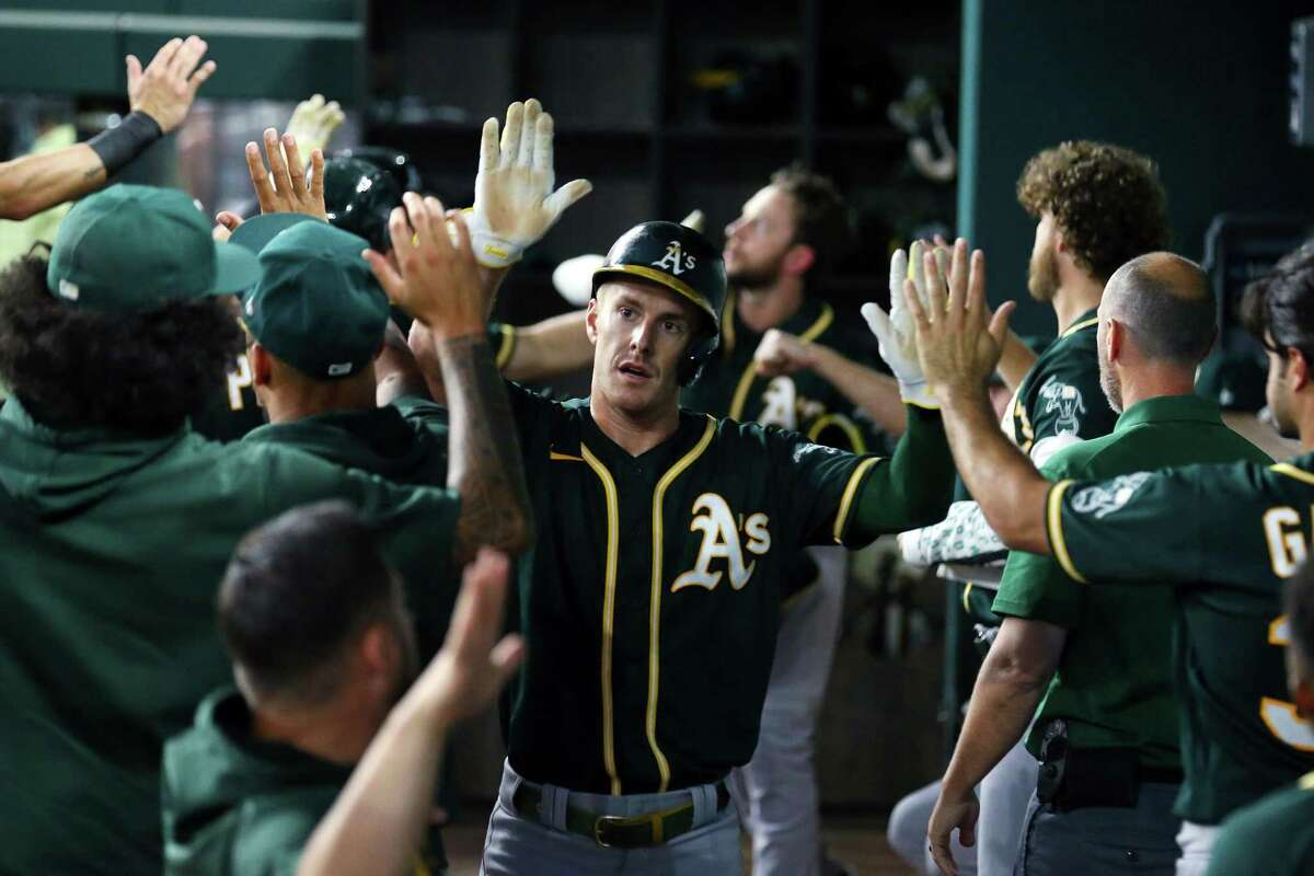 ARLINGTON, TEXAS - JUNE 22: Mark Canha #20 of the Oakland Athletics is greeted in the dugout after scoring in the second inning against the Texas Rangers at Globe Life Field on June 22, 2021 in Arlington, Texas. (Photo by Richard Rodriguez/Getty Images)