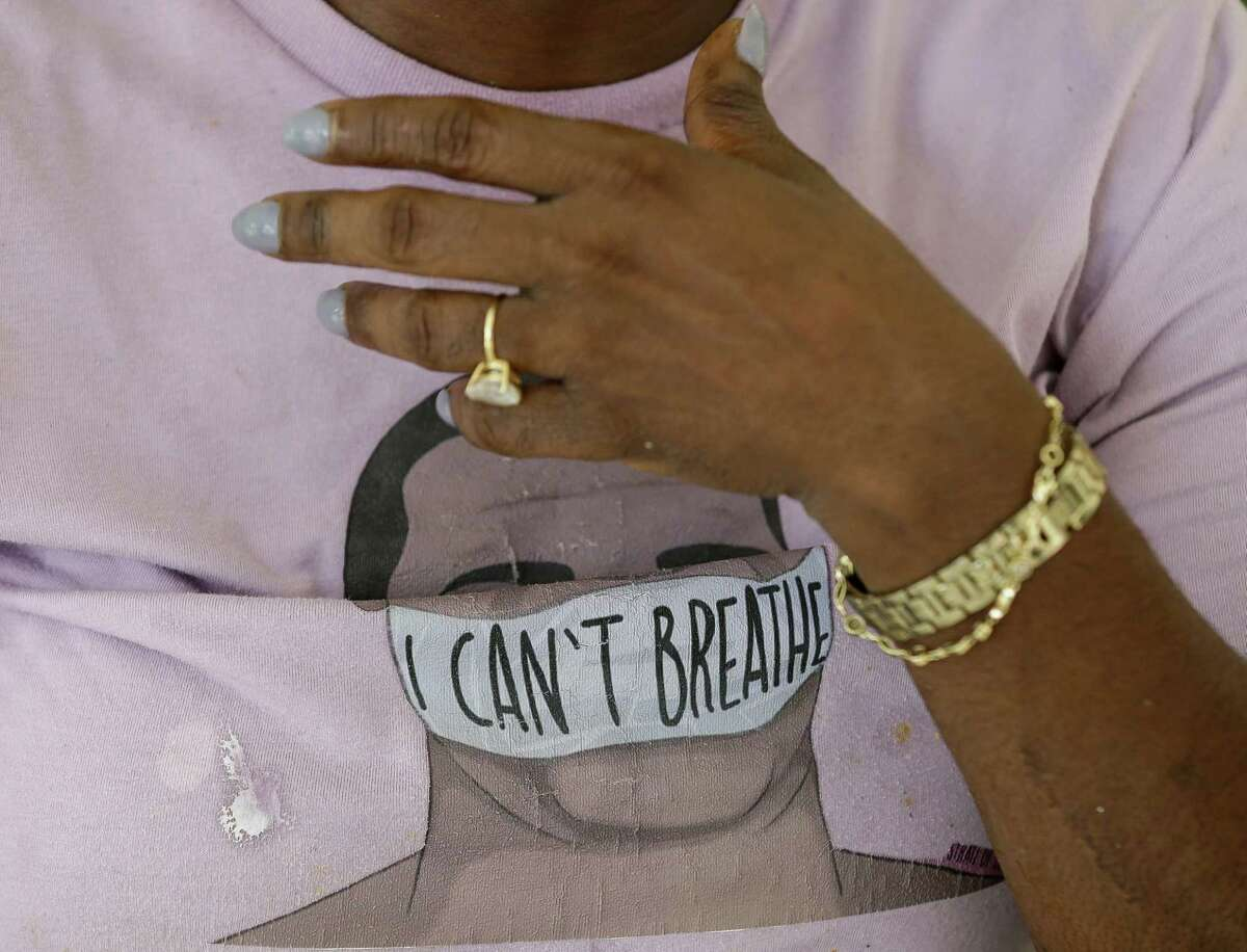 """Kim Hewitt wears a George Floyd shirt that read """"I Can't Breathe"""" while listening to the sentencing proceedings of Derek Chauvin - the former Minneapolis Police officer who killed Floyd - while sitting at her food truck, Brunch Box, on Friday, June 25, 2021, in Third Ward, Houston."""