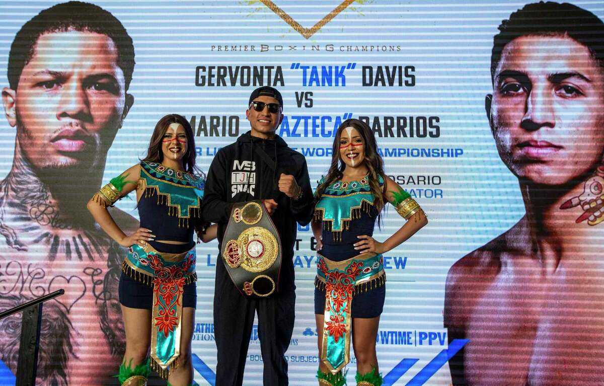 """Mario ?'El Azteca?"""" Barrios, the undefeated WBA Super Lightweight boxing champion, poses Tuesday afternoon June 22, 2021, with two models in front of a large screen during a brief stop at the San Antonio airport to promote his Saturday fight against Two-Division World Champion Gervonta ?'Tank?"""" Davis."""