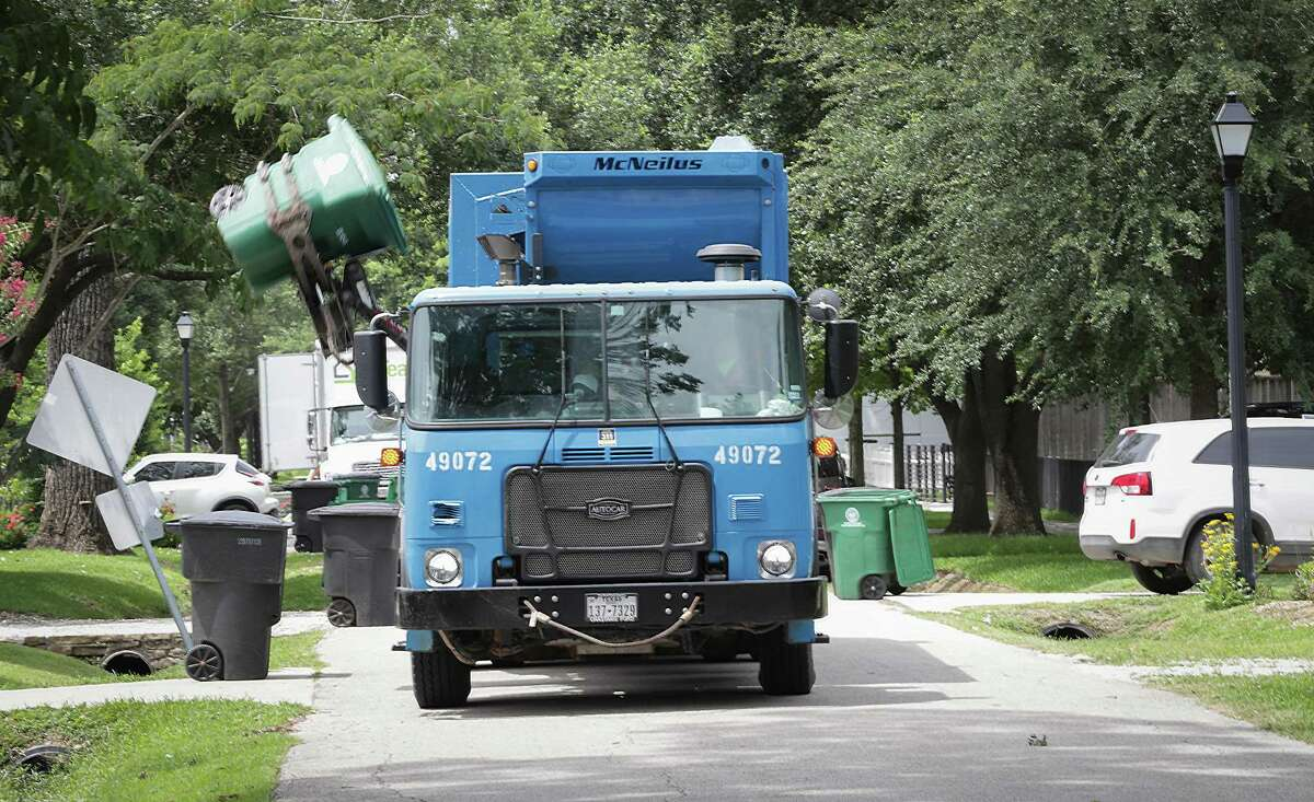 A city recycling truck picks up a bin on Allston St., near 8th St., on Thursday. Houston now is offering a $3,000 signing bonus as the city looks to hire more than 100 people to bolster Solid Waste's ranks.