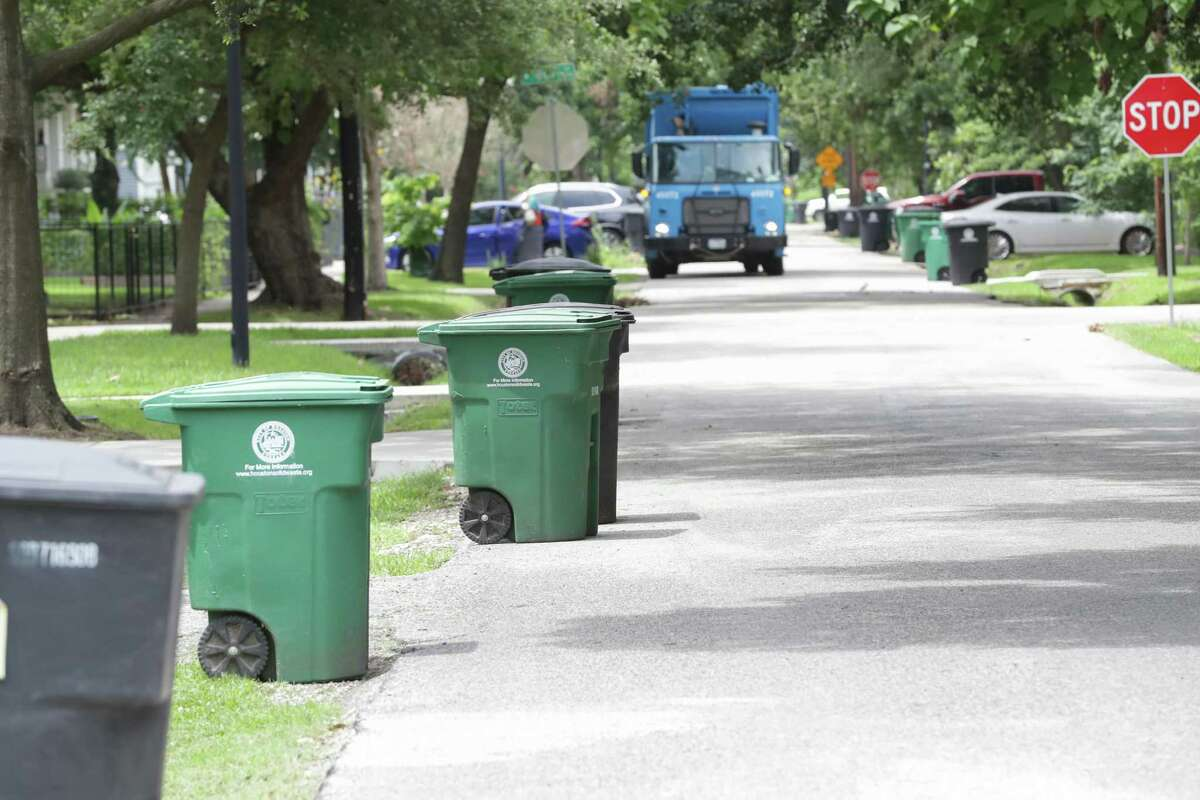 A city recycling truck picks up a bin on Allston, near 8th Street, on Thursday. Houston now is offering a $3,000 signing bonus as the city looks to hire more than 100 people to bolster Solid Waste's ranks.