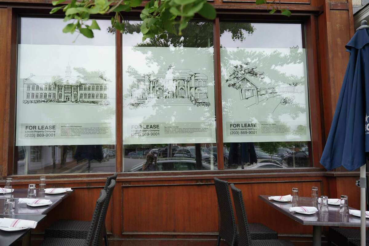 The former New Balance store at 28 Main Street has received six panels of the wallpaper designed to spruce up empty storefronts in the village of New Canaan. The picture was taken on June 25, 2021. The tables belong to Spiga restaurant next door.