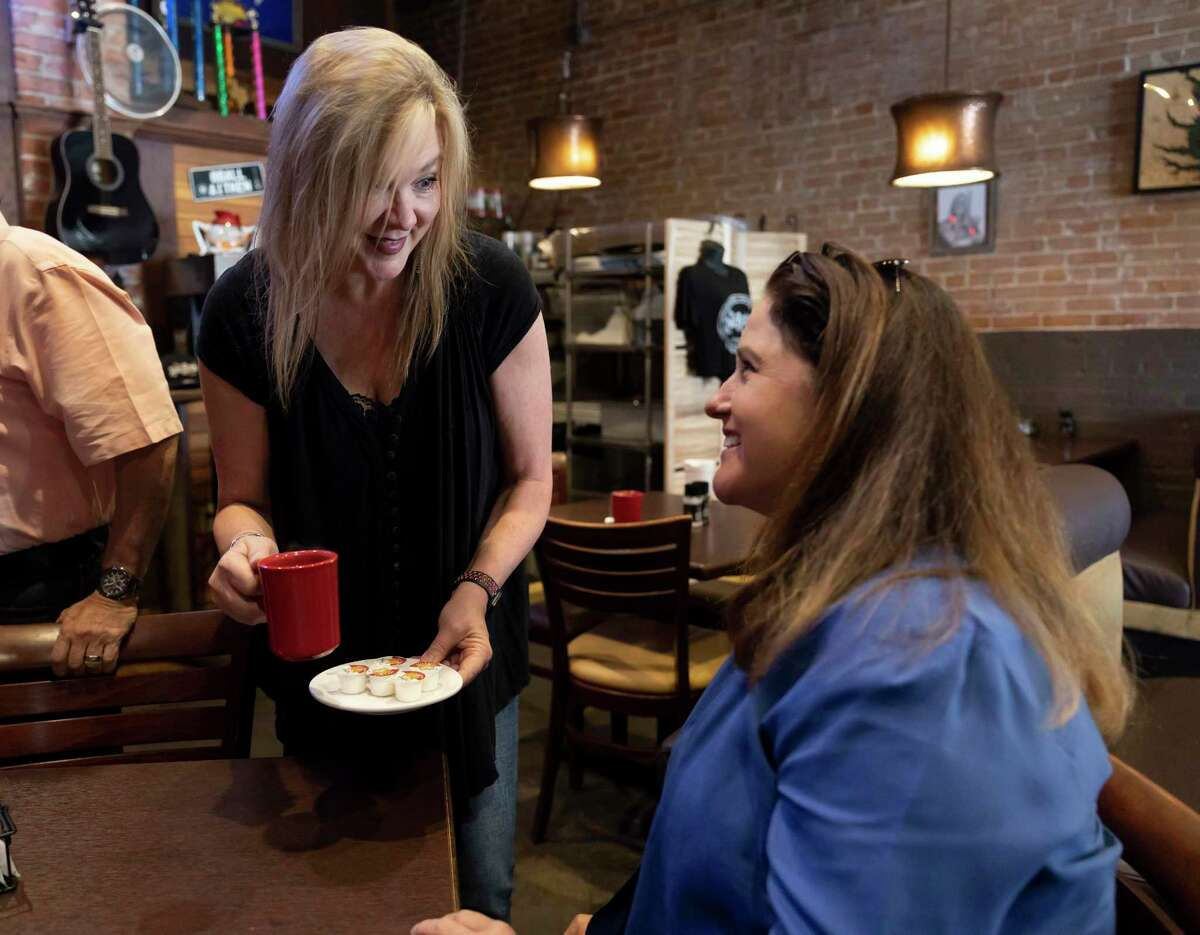 Debbie Glenn, owner of Red Brick Tavern, left, serves Laura Watson a cup of coffee at the Red Brick Tavern, Tuesday, June 8, 2021, in downtown Conroe. The restaurant now opens at 7 a.m. for breakfast.