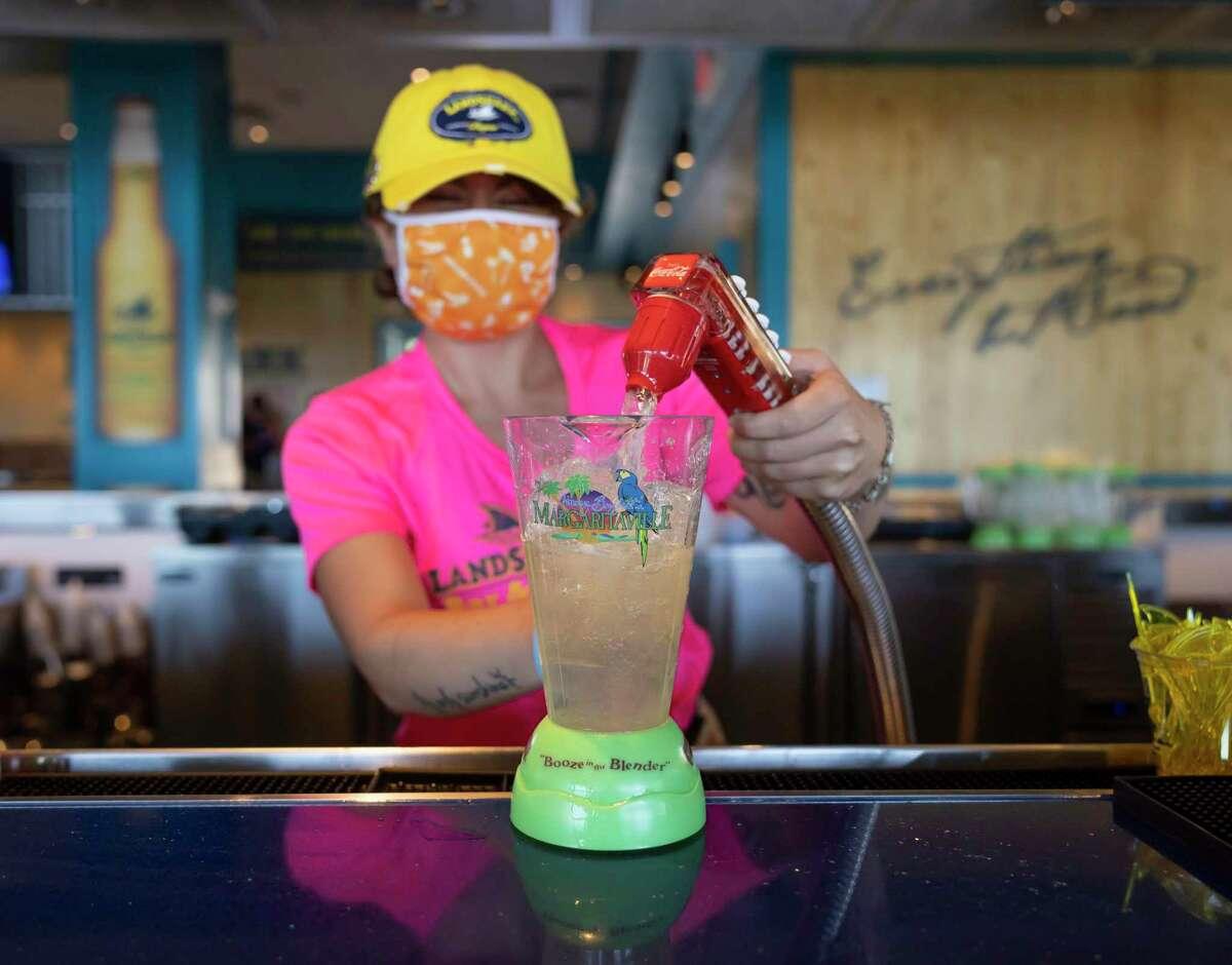 Bella Peppe, bartender at Margaritaville's LandShark Bar & Grill in Lake Conroe, makes a margarita on the rocks. Margaritaville still has more than 100 positions open at the resort.