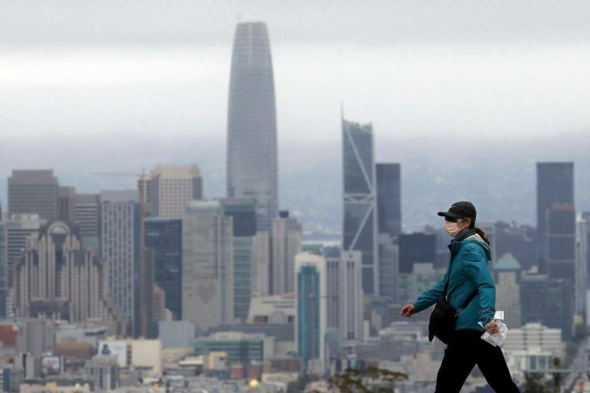 A woman wears a mask during the coronavirus outbreak while crossing a street in front of the skyline in San Francisco, Saturday, April 4, 2020.