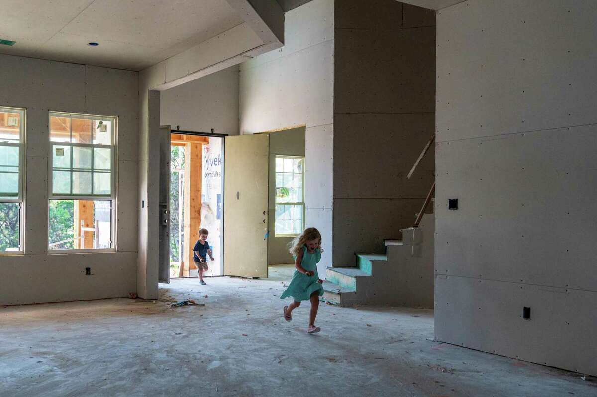 Emma, 4, and Brady, 2, Rubbicco run through the house their parents are building in Austin.