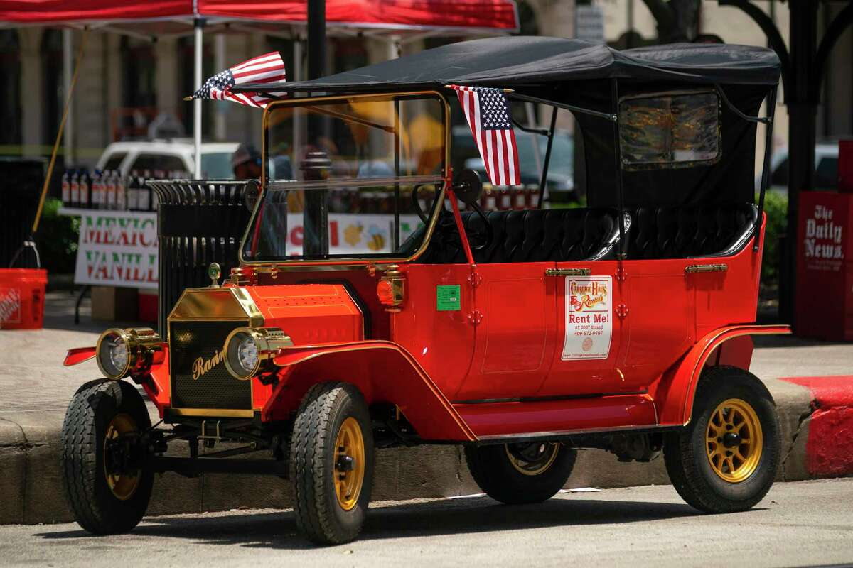 People look at one of the rentals offered by Carriage Haus Rentals on the Strand on Galveston Island on Wednesday, June 23, 2021, in Galveston. Carriage Haus Rentals are offering rentals of the electric golf carts that are replicas of a 1908 Model T.
