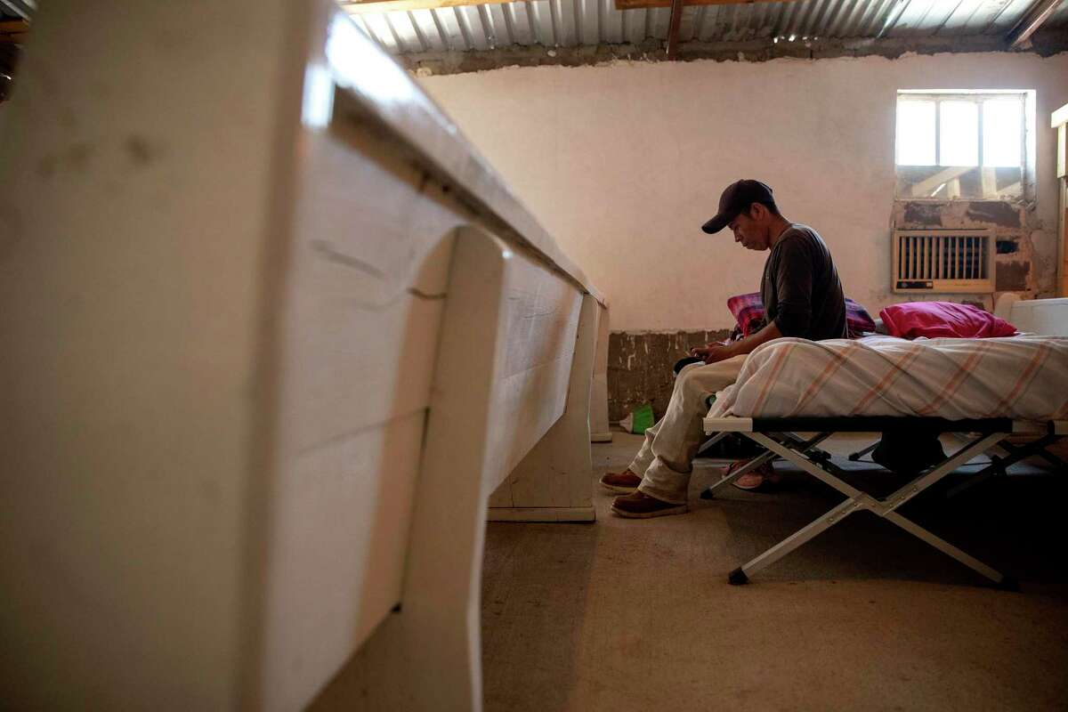 Lucio Lopez, a migrant from the Mayan highlands of Guatemala, looks at photos of his family inside the stuffy room at the Ojinaga shelter.