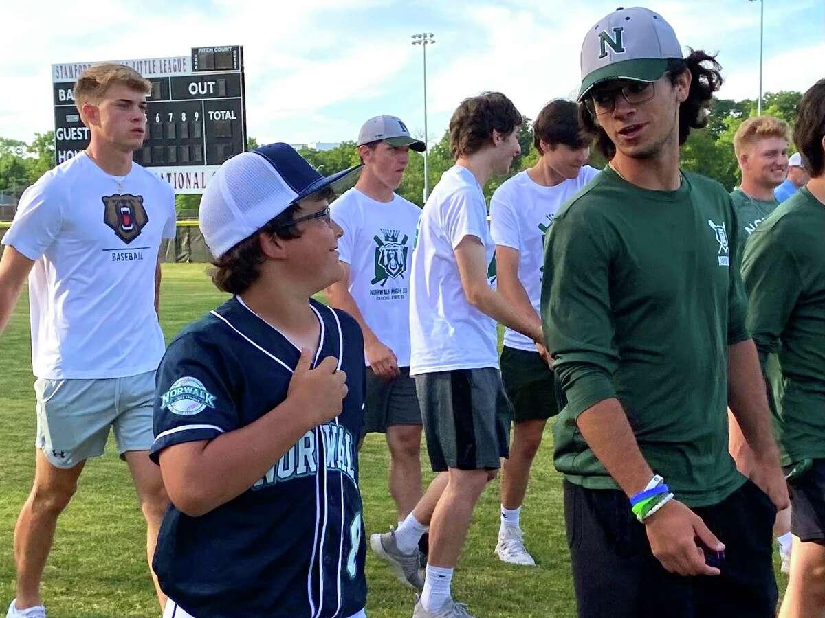 Norwalk Little League played Ryan Smith walks off the field with Norwalk High baseball player Ethan Platt.