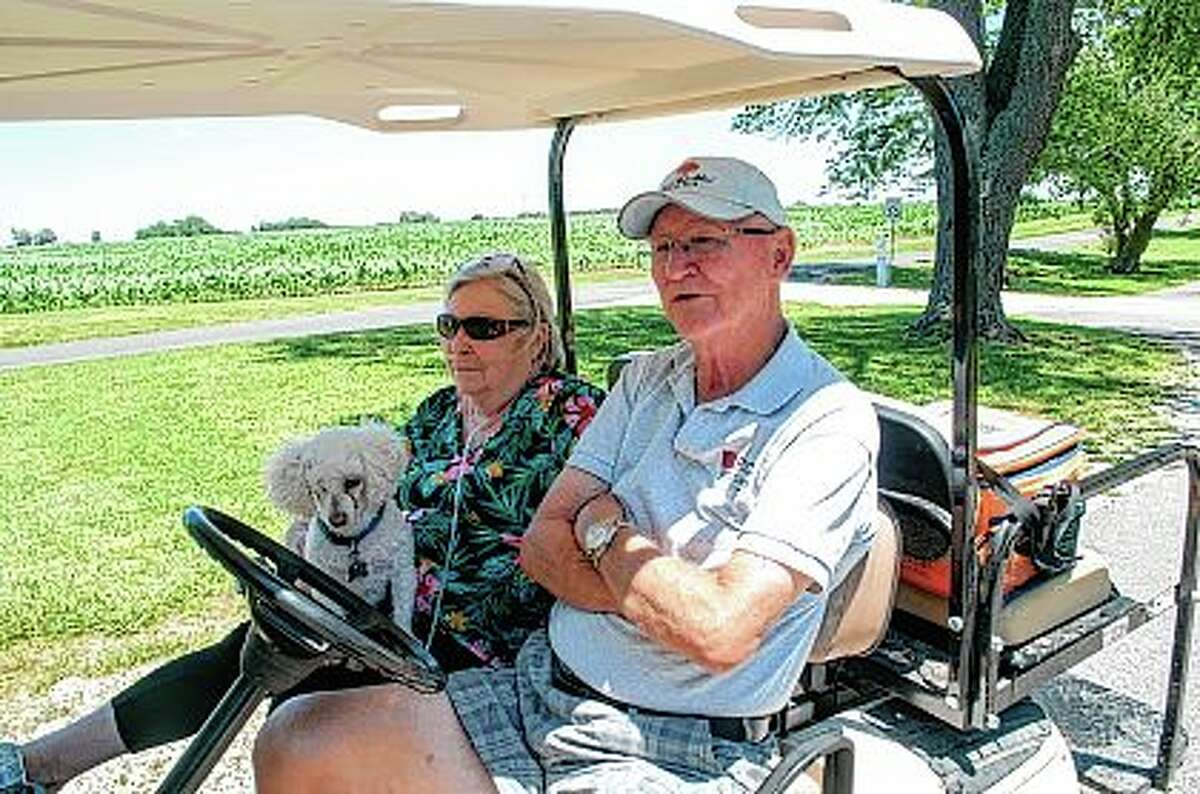 Bob and Barb Jenkins, along with their dog, Rowdy, sit in their golf cart. The Jenkins started staying at Lake Jacksonville in 1970.