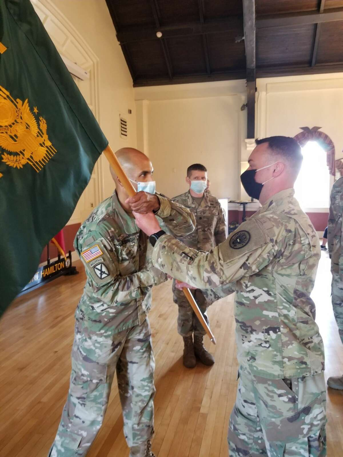 New York Army National Guard Maj. Dan Colomb, right, accepts the flag of the 24th Weapons of Mass Destruction Civil Support Team at Fort Hamilton in Brooklyn, during a change of command.