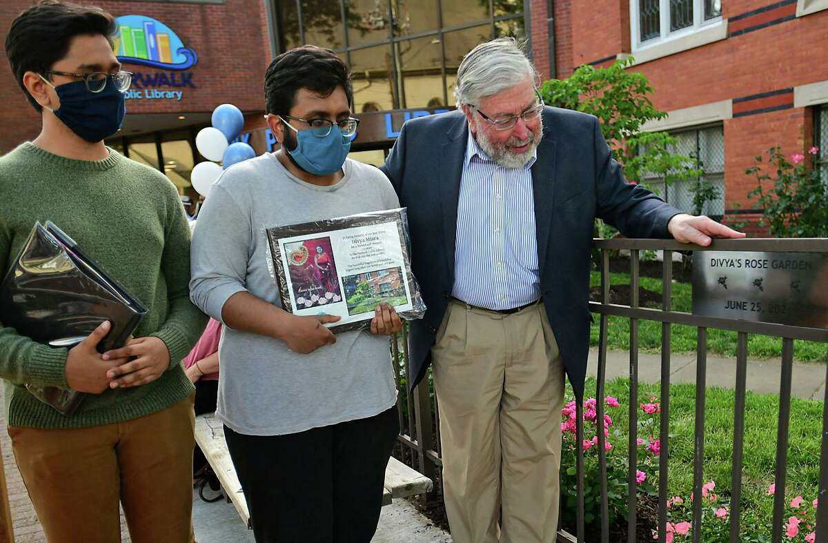Library Board President Alex Knopp, right, presents the dedication plaque to Bharat Misra and Akshat Misra as nearly 100 people gathered for the dedication ceremony for the rose garden renamed after their mother, Divya Misra, a Norwalk Public Library employee, on Friday at the library in Norwalk. Divya Misra was killed by her husband in May, according to authorities.