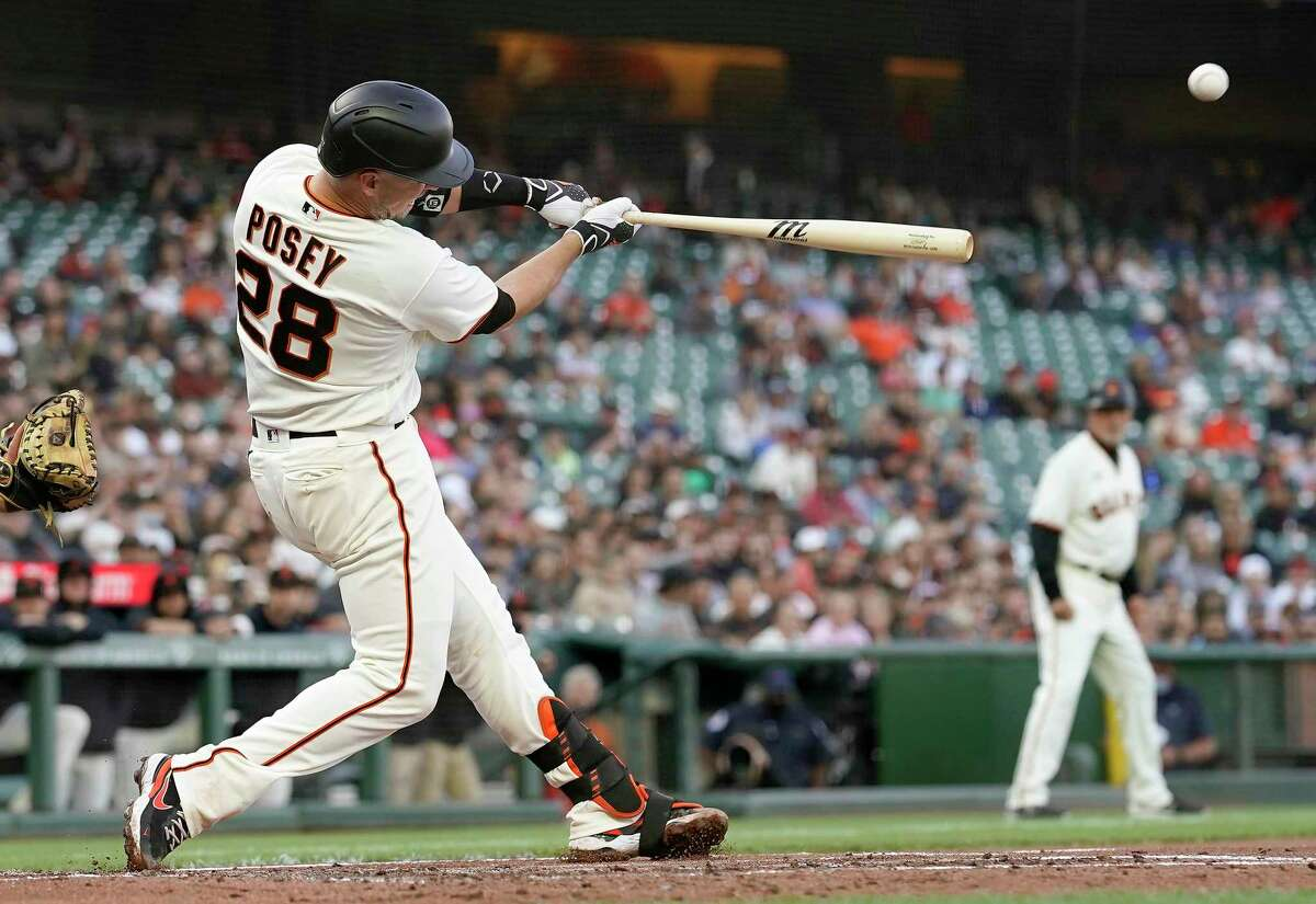 Buster Posey (28) of the San Francisco Giants hits a three-run home run against the Arizona Diamondbacks in the bottom of the first inning at Oracle Park on June 16, 2021, in San Francisco. (Thearon W. Henderson/Getty Images/TNS)