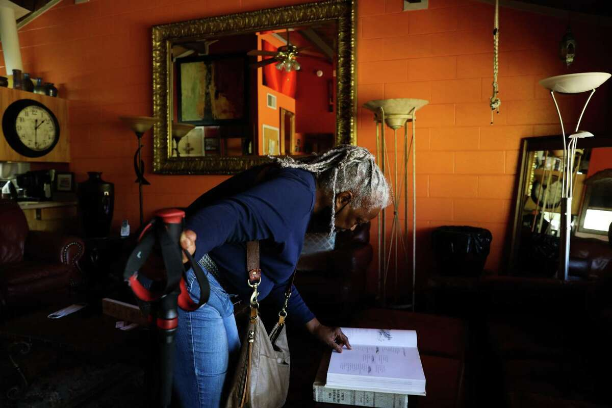 Longtime Golden Gate Village resident Royce McLemore looks at an architecture book in her Golden Gate Village apartment. McLemore has led a call for the county to address the property's maintenance issues.